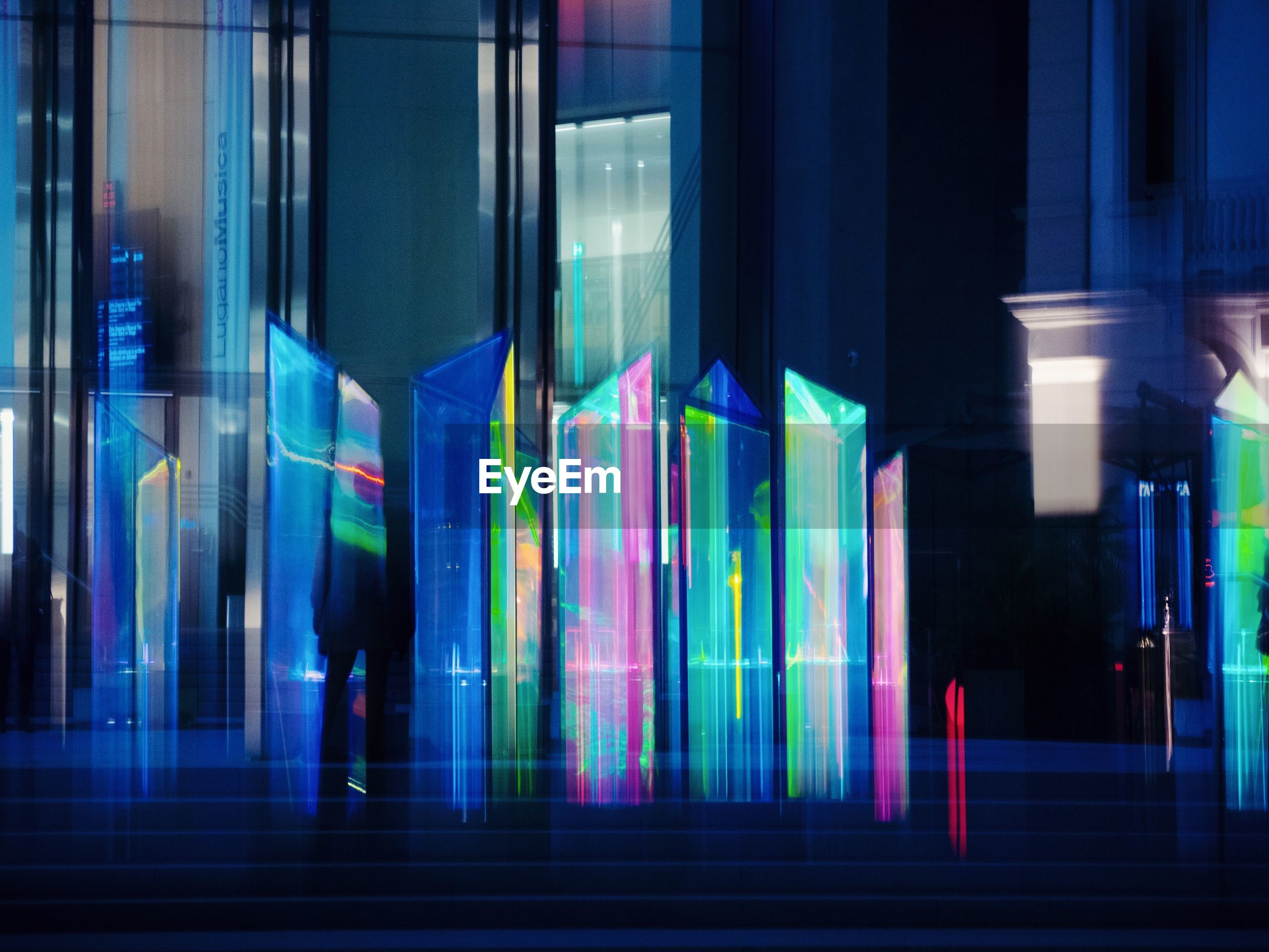 illuminated, multi colored, night, glass - material, motion, architecture, built structure, city, reflection, building exterior, glowing, blue, transparent, blurred motion, no people, neon, lighting equipment, window, light - natural phenomenon, building, modern, nightlife, glass, light, purple