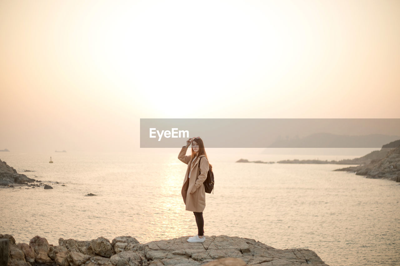 water, sea, sky, rock, one person, rock - object, full length, beauty in nature, solid, standing, scenics - nature, lifestyles, leisure activity, young adult, real people, nature, women, beach, outdoors, hairstyle
