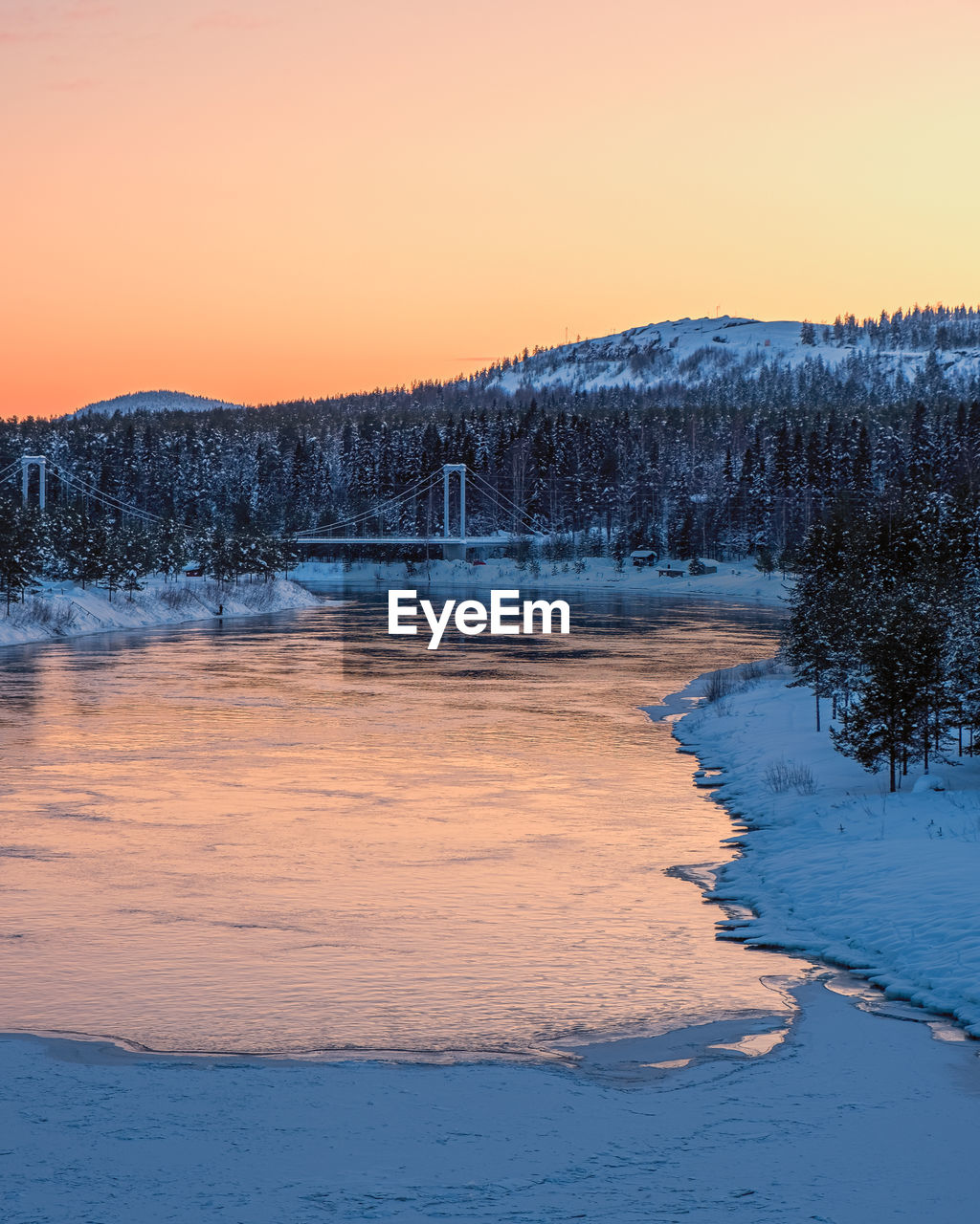 SCENIC VIEW OF FROZEN LAKE AGAINST ORANGE SKY DURING WINTER