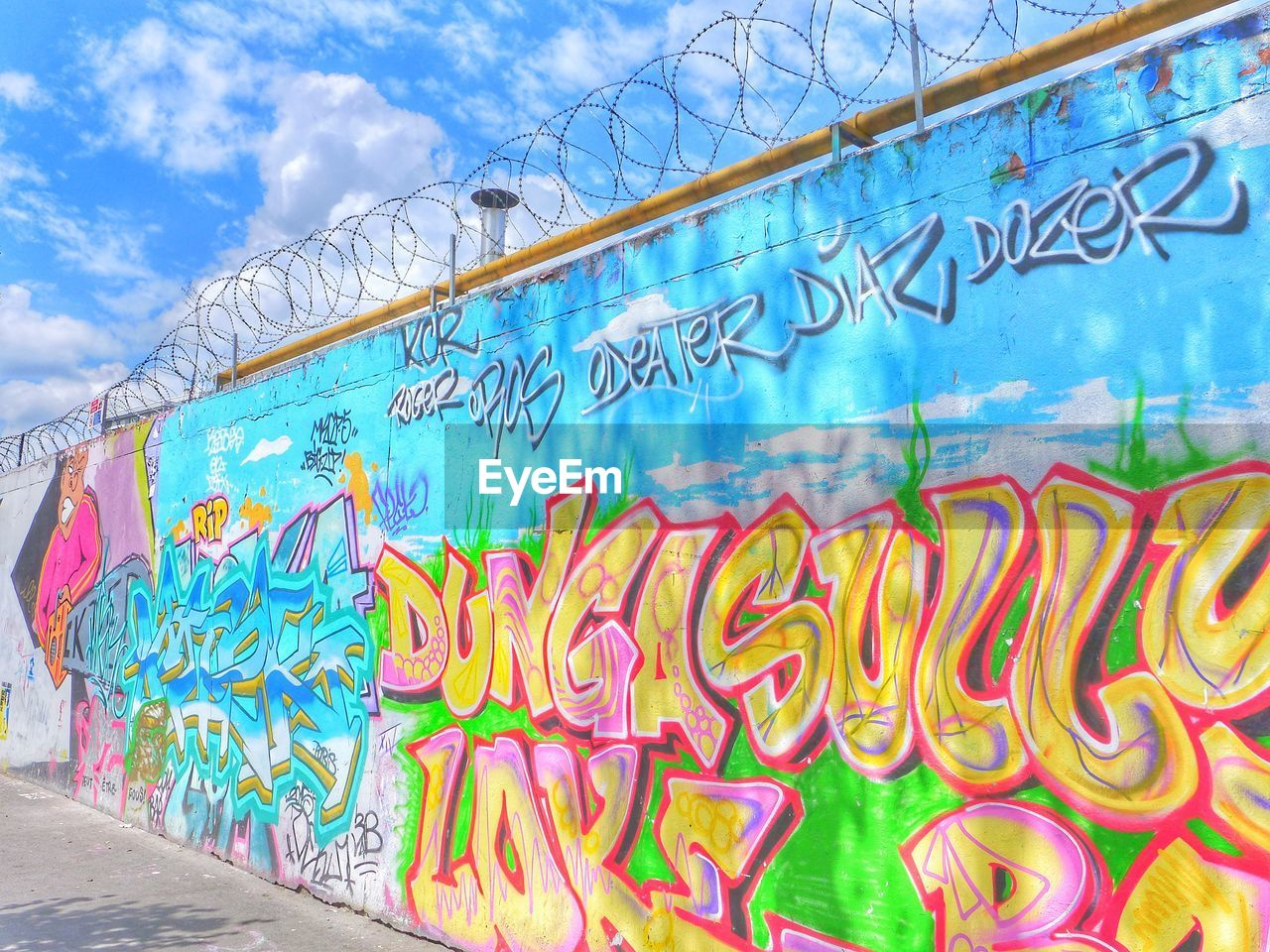 graffiti, multi colored, creativity, text, art and craft, no people, cloud - sky, day, street art, water, blue, western script, nature, outdoors, architecture, sky, wall - building feature, communication, built structure