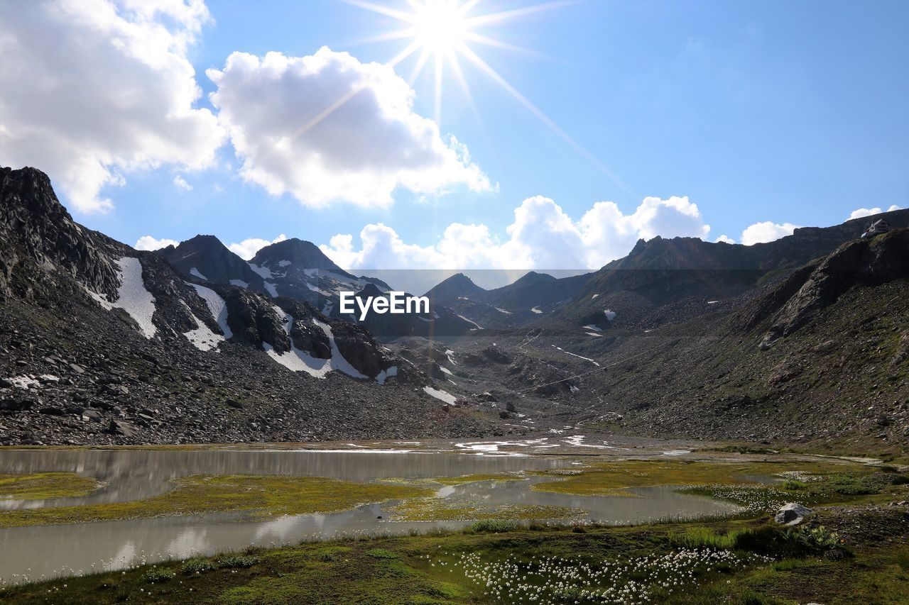 mountain, sky, beauty in nature, water, environment, landscape, lake, scenics - nature, nature, mountain range, cloud - sky, day, tranquil scene, sunlight, reflection, tranquility, no people, non-urban scene, outdoors, lens flare, mountain peak, bright, snowcapped mountain