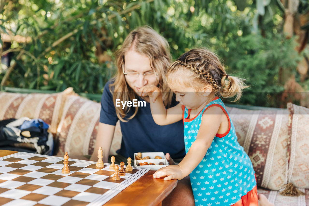 Girl standing by father arranging chess pieces on board