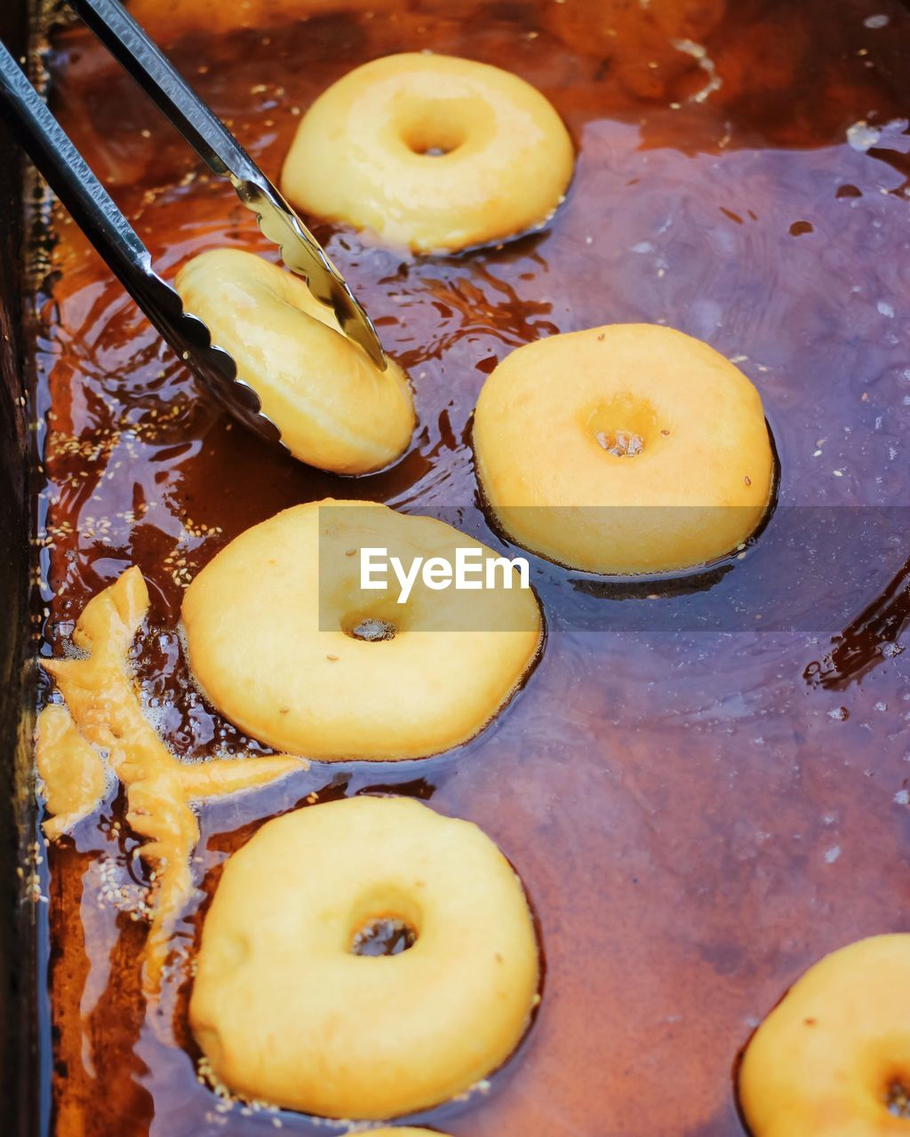 High Angle View Of Donuts Being Fried In Oil At Market