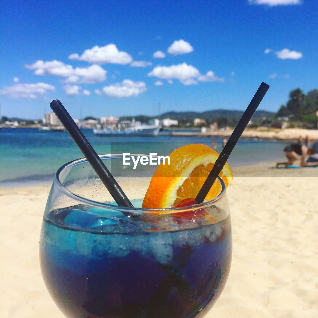 beach, drinking straw, food and drink, sky, focus on foreground, refreshment, incidental people, sea, drink, day, close-up, sand, drinking glass, blue, outdoors, cloud - sky, vacations, freshness, horizon over water, beauty in nature, nature, healthy eating, water, people
