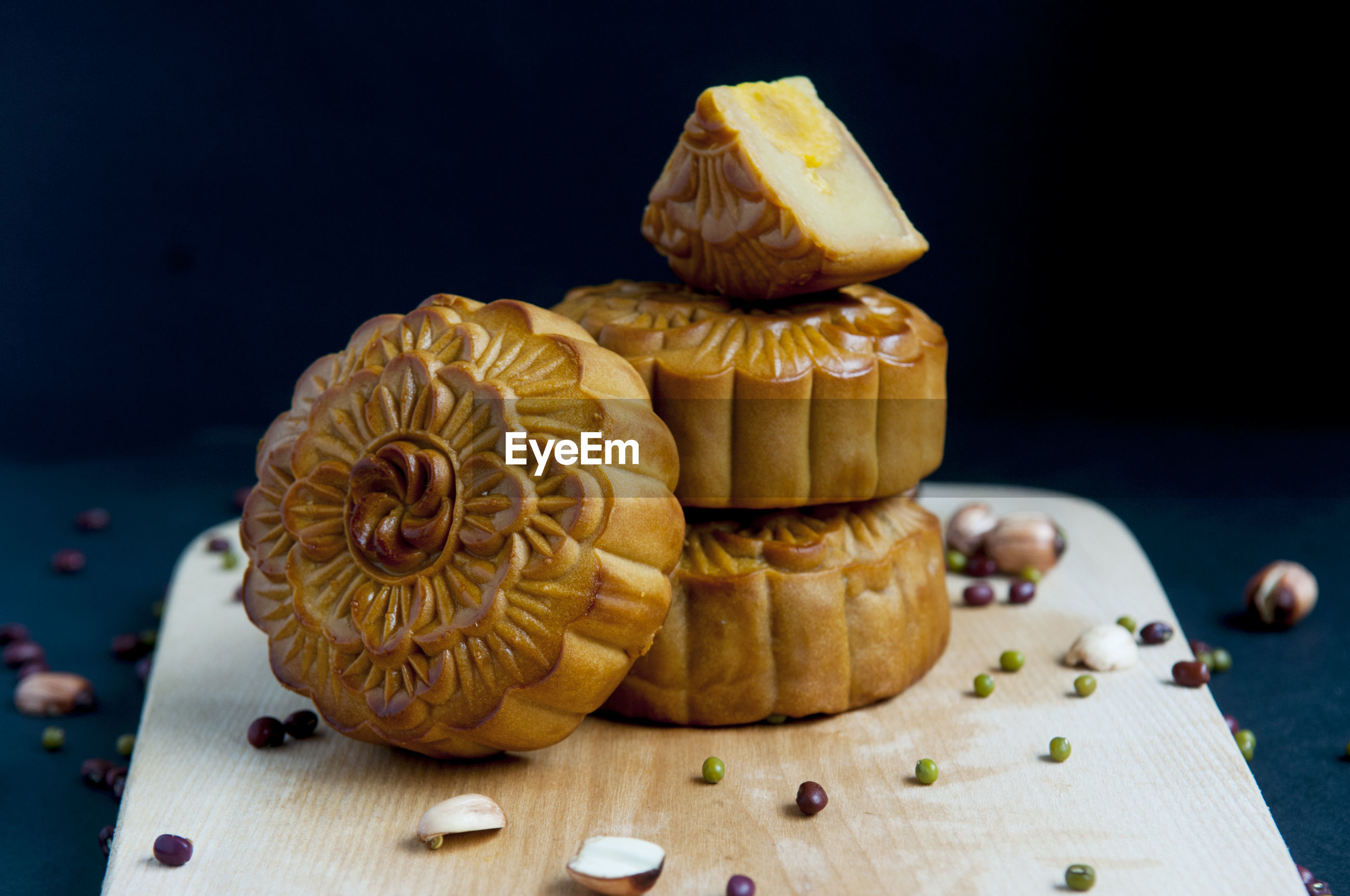 Close-up of moon cakes with seeds on serving board against black background