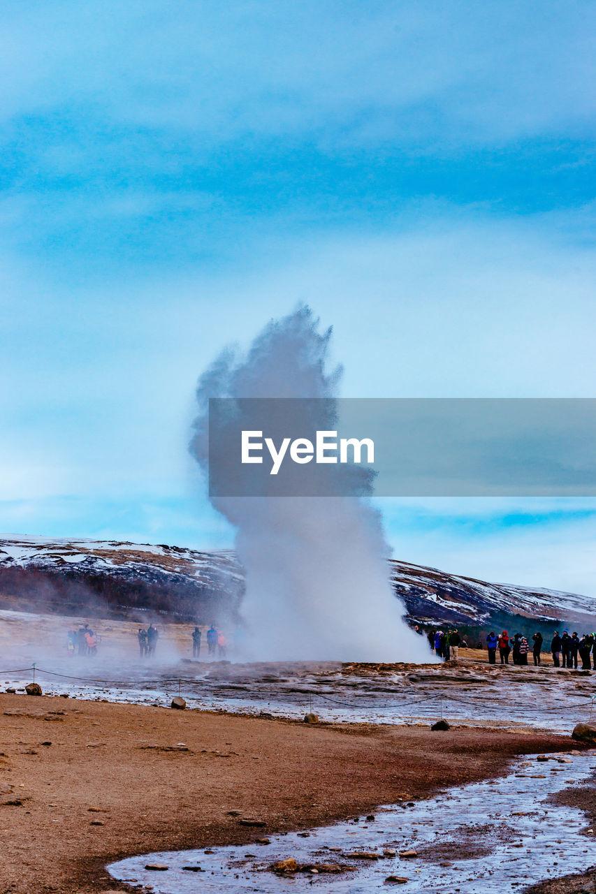 People Looking At Splashing Geyser Against Sky