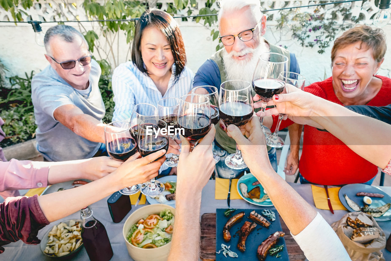 smiling, alcohol, group of people, wine, drink, men, togetherness, women, glass, adult, happiness, food and drink, males, wineglass, enjoyment, leisure activity, refreshment, celebratory toast, celebration, mature adult, mature men, drinking, social gathering