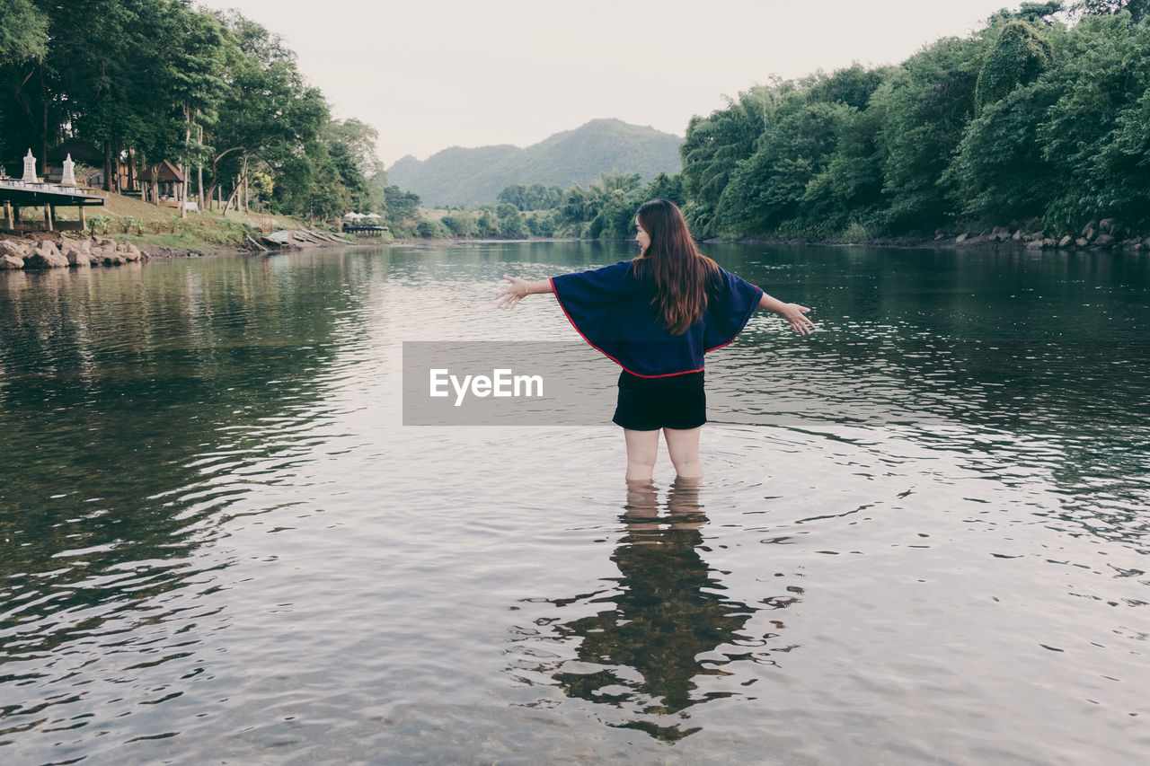 Rear View Of Woman Standing In Lake Against Sky