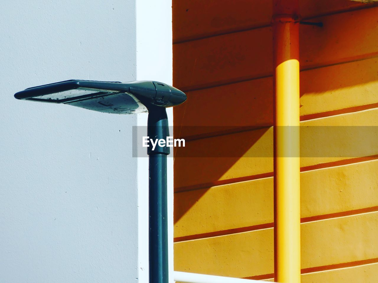 wall - building feature, built structure, day, no people, architecture, outdoors, metal, building exterior, yellow, security, handle, protection, safety, sunlight, close-up, nature, wall, pole, blue, shadow