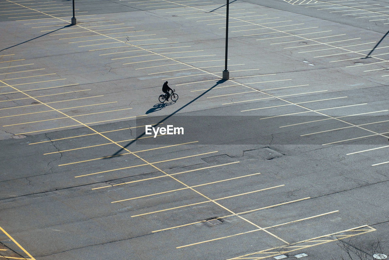 High Angle View Of Man Riding Bicycle On Road