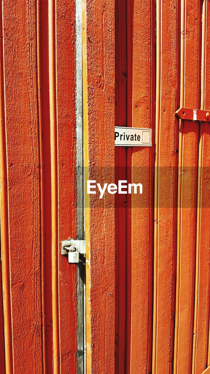 Private Text On Closed Orange Door During Sunny Day