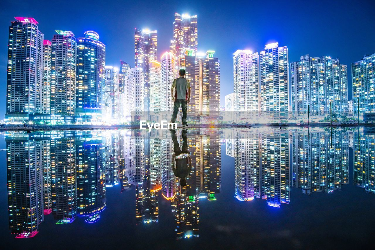 DIGITAL COMPOSITE IMAGE OF ILLUMINATED MODERN BUILDINGS IN CITY