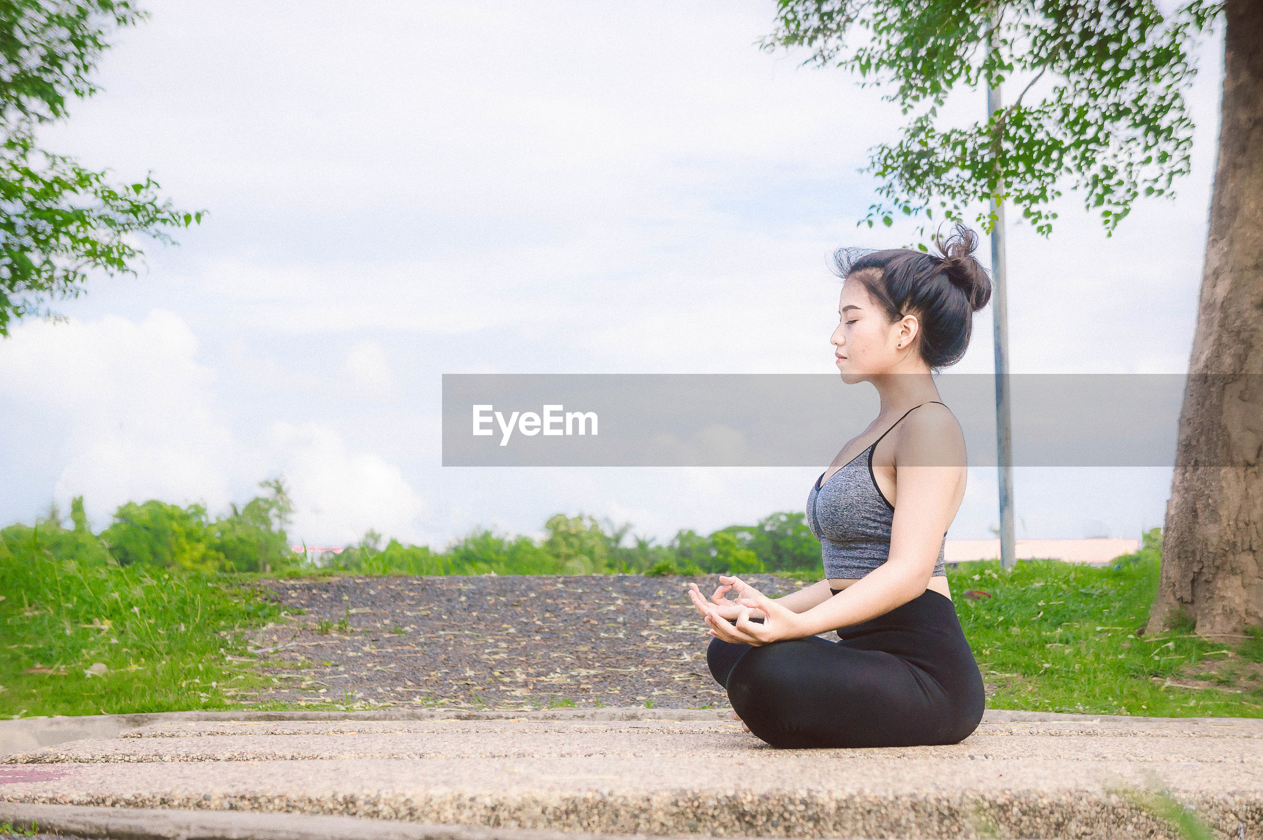 Side view of woman meditating against sky