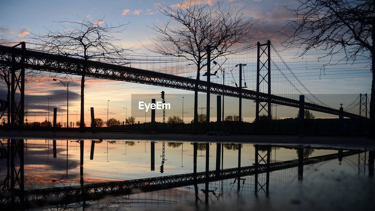 built structure, architecture, connection, reflection, bridge - man made structure, sky, water, sunset, tree, river, waterfront, no people, outdoors, travel destinations, bare tree, industry, city, nature, building exterior, electricity pylon, day