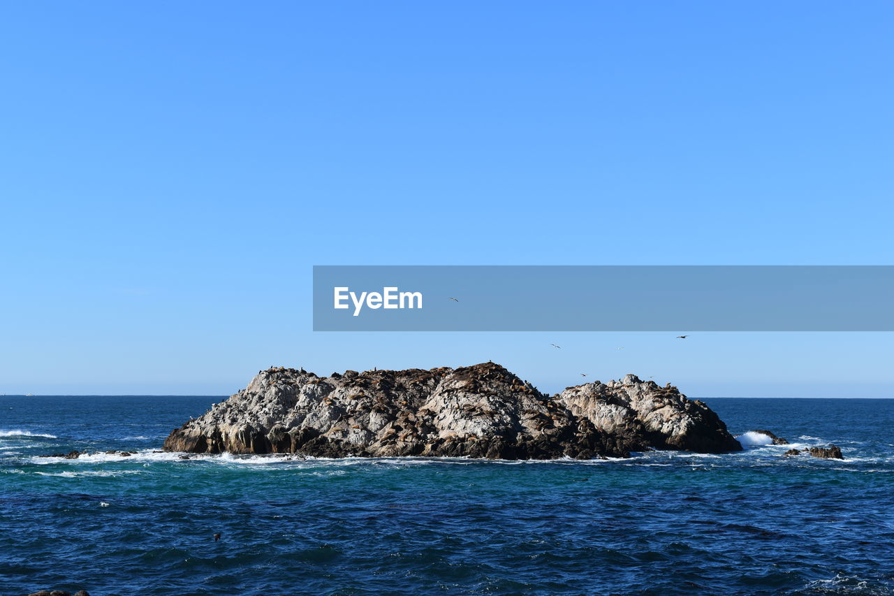 sea, horizon over water, blue, nature, beauty in nature, scenics, clear sky, tranquility, water, copy space, tranquil scene, waterfront, rock - object, no people, outdoors, scenery, sky, day, blue sky