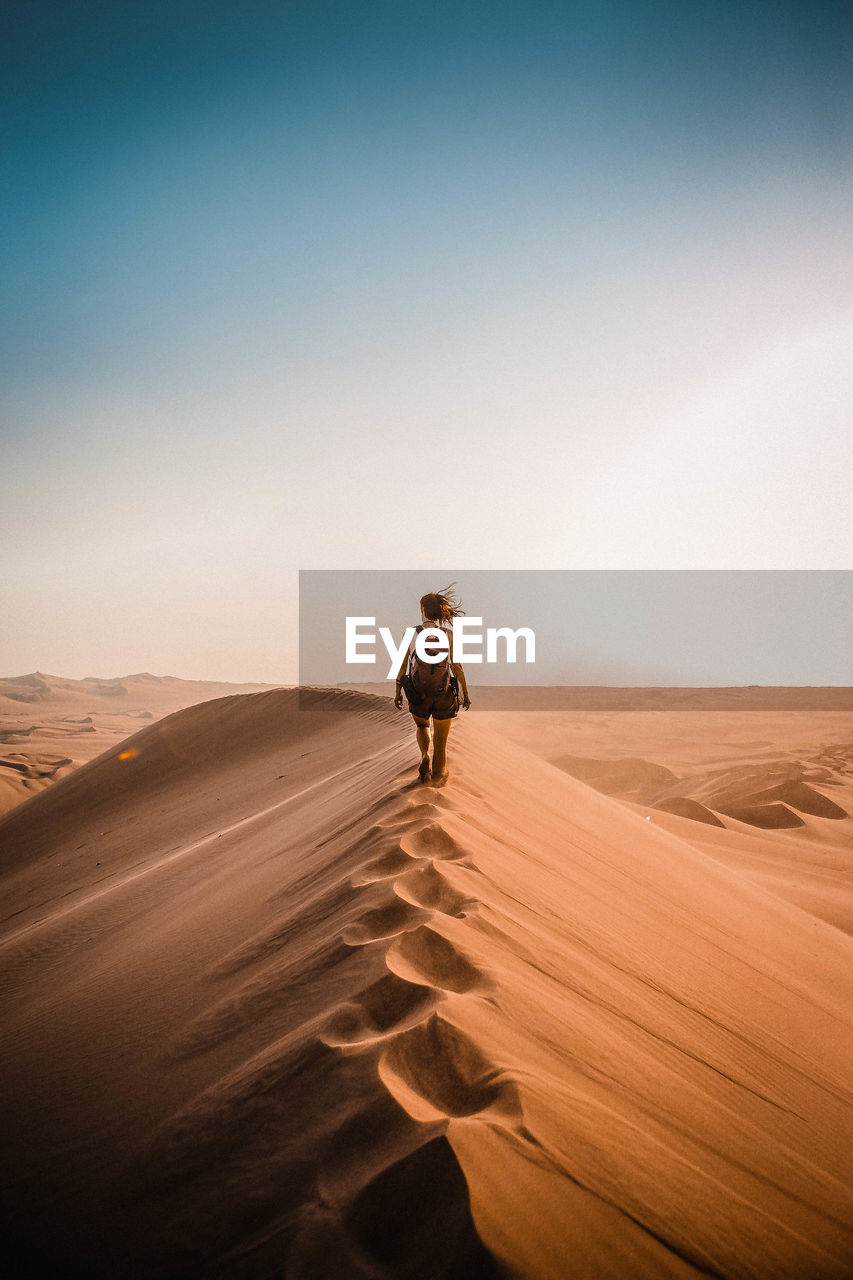 Rear View Of Woman Walking On Sand Dune In Desert