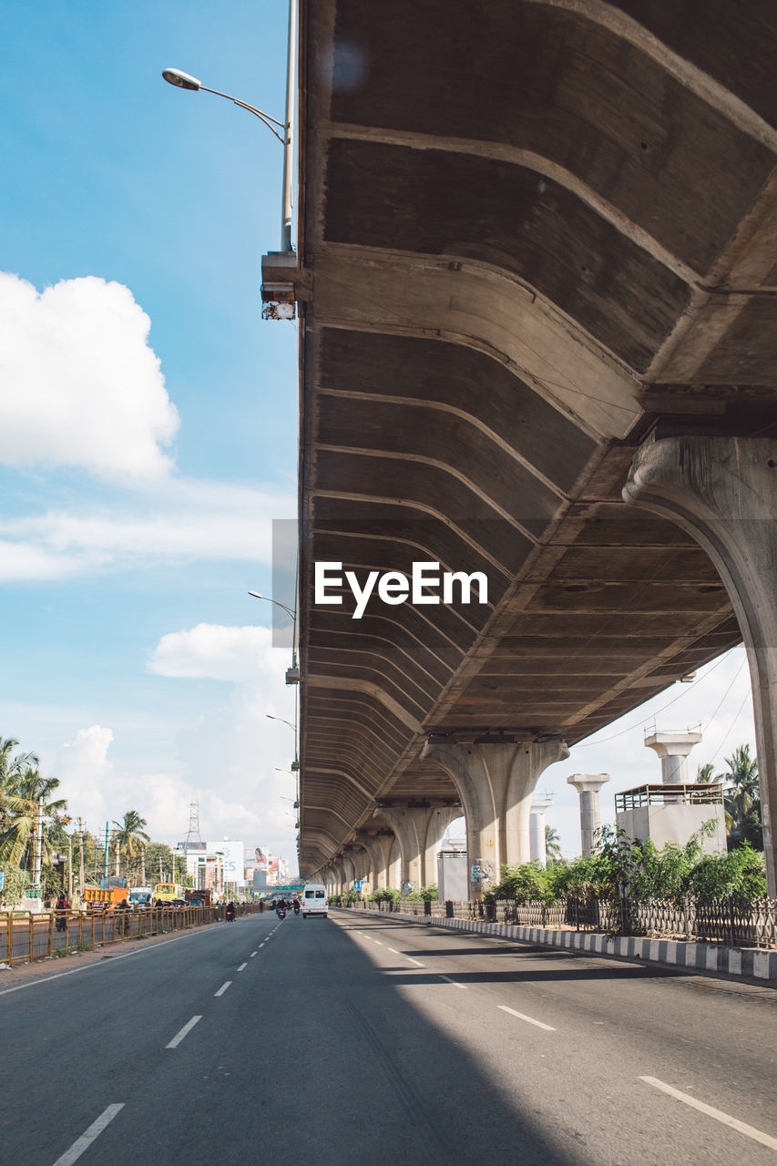 architecture, transportation, built structure, road, the way forward, connection, sky, bridge, direction, bridge - man made structure, cloud - sky, city, nature, street, day, diminishing perspective, engineering, arch, sign, mode of transportation, outdoors, architectural column, overpass