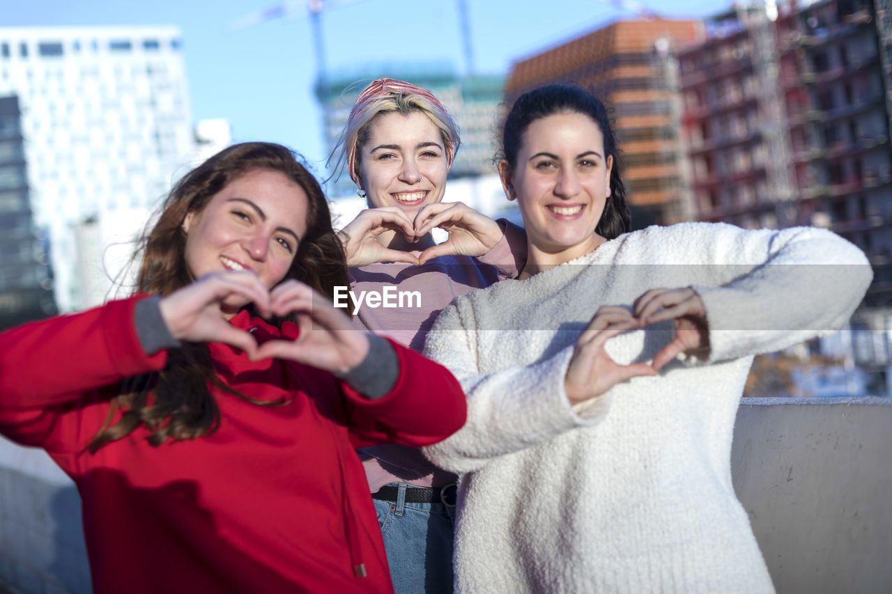 Portrait of smiling women forming heart shapes