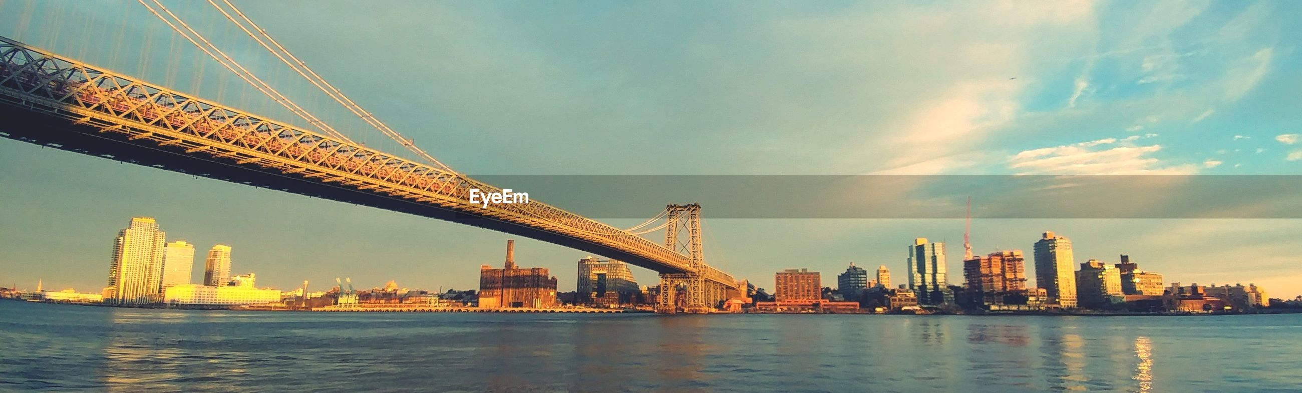Panoramic view of bridge over river against sky in city during sunset