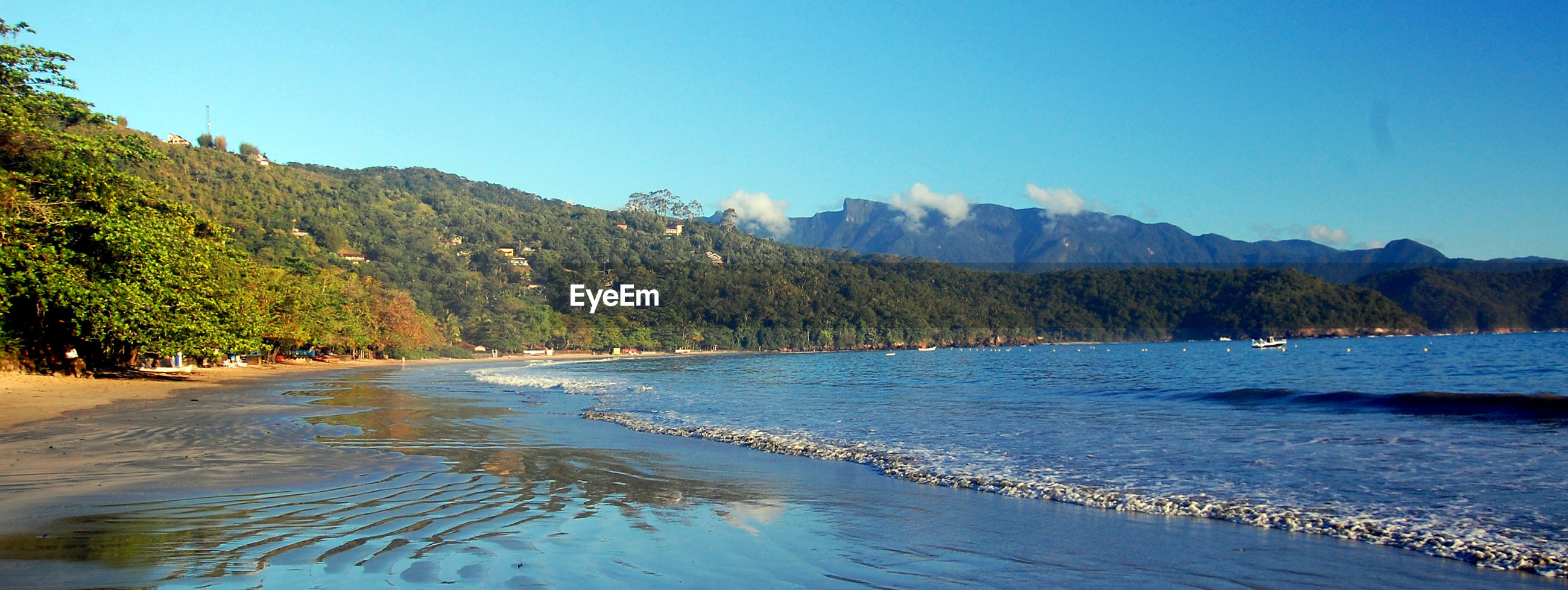 VIEW OF CALM BEACH AGAINST MOUNTAIN RANGE