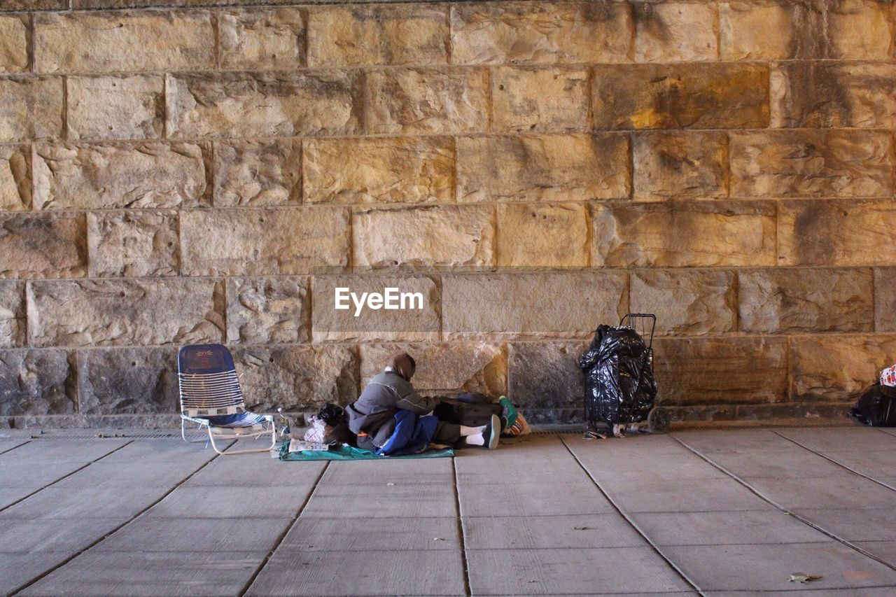 Homeless person sitting on sidewalk against stone wall
