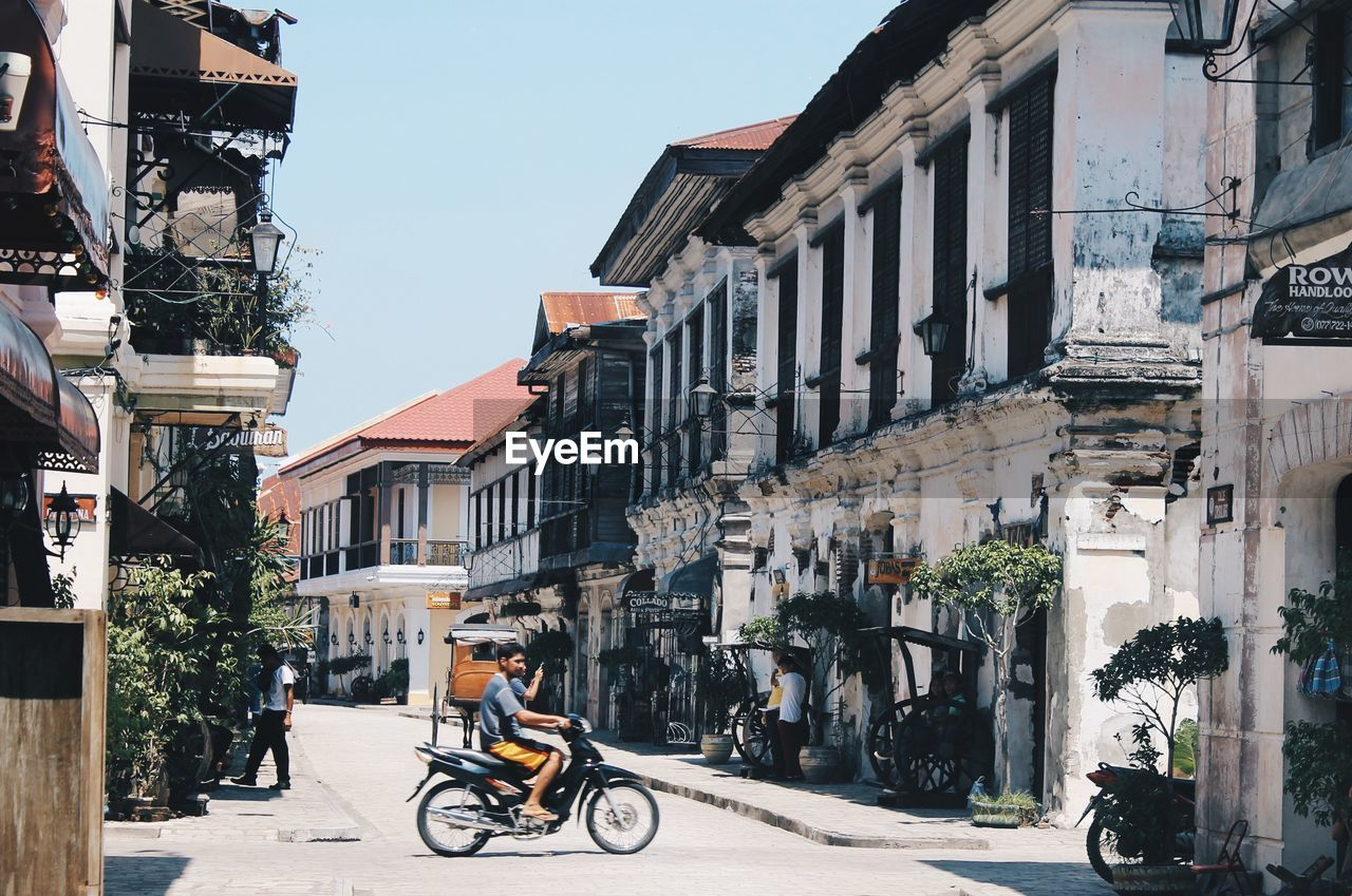 architecture, building exterior, street, transportation, mode of transport, bicycle, land vehicle, built structure, outdoors, real people, day, city, road, stationary, motorcycle, men, clear sky, scooter, sky, tree, people