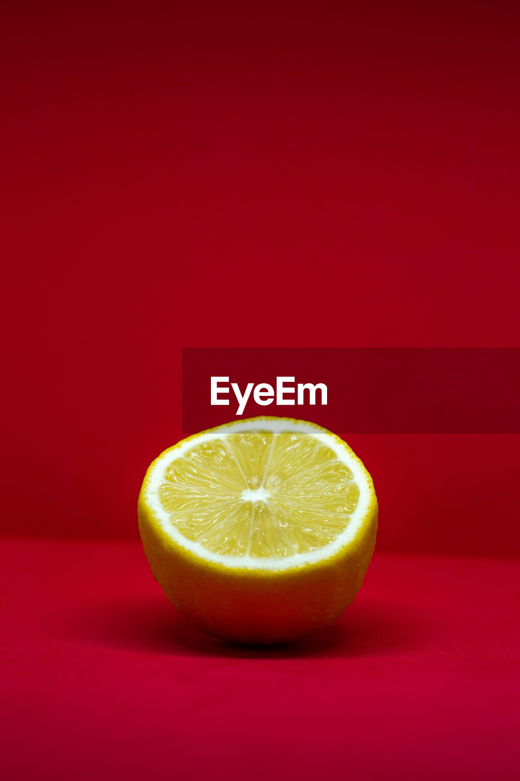 Close-up of lemon slice against red background
