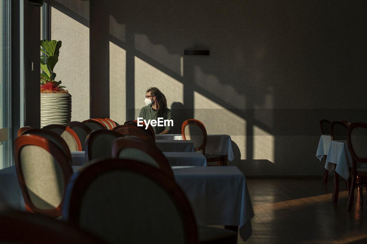 WOMAN SITTING IN EMPTY ROOM