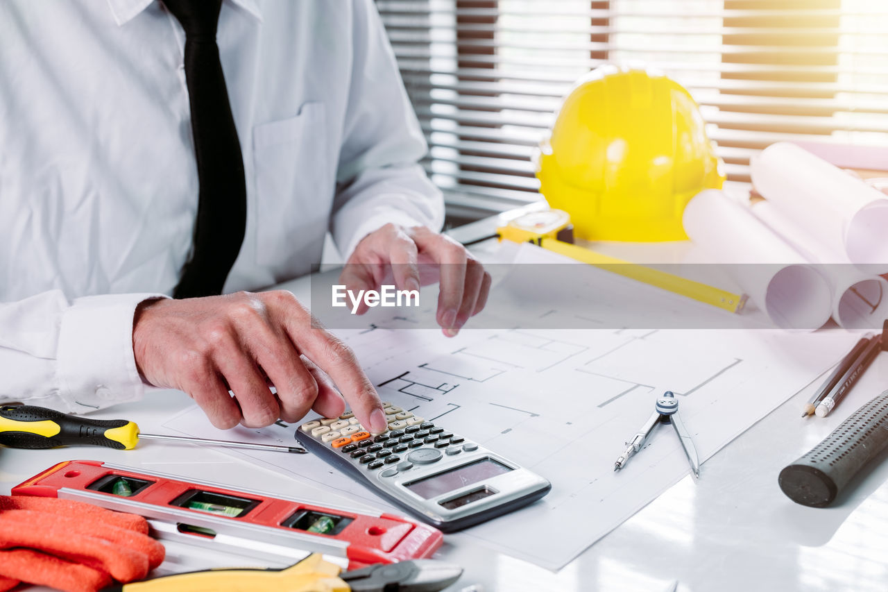 occupation, real people, indoors, working, one person, table, men, business, midsection, pen, adult, human hand, hand, holding, technology, human body part, communication, computer, professional occupation, blueprint