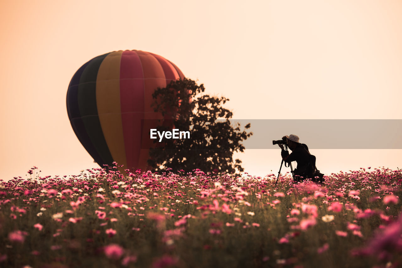 Scenic View Of Hot Air Balloon At Field Against Clear Sky During Sunset