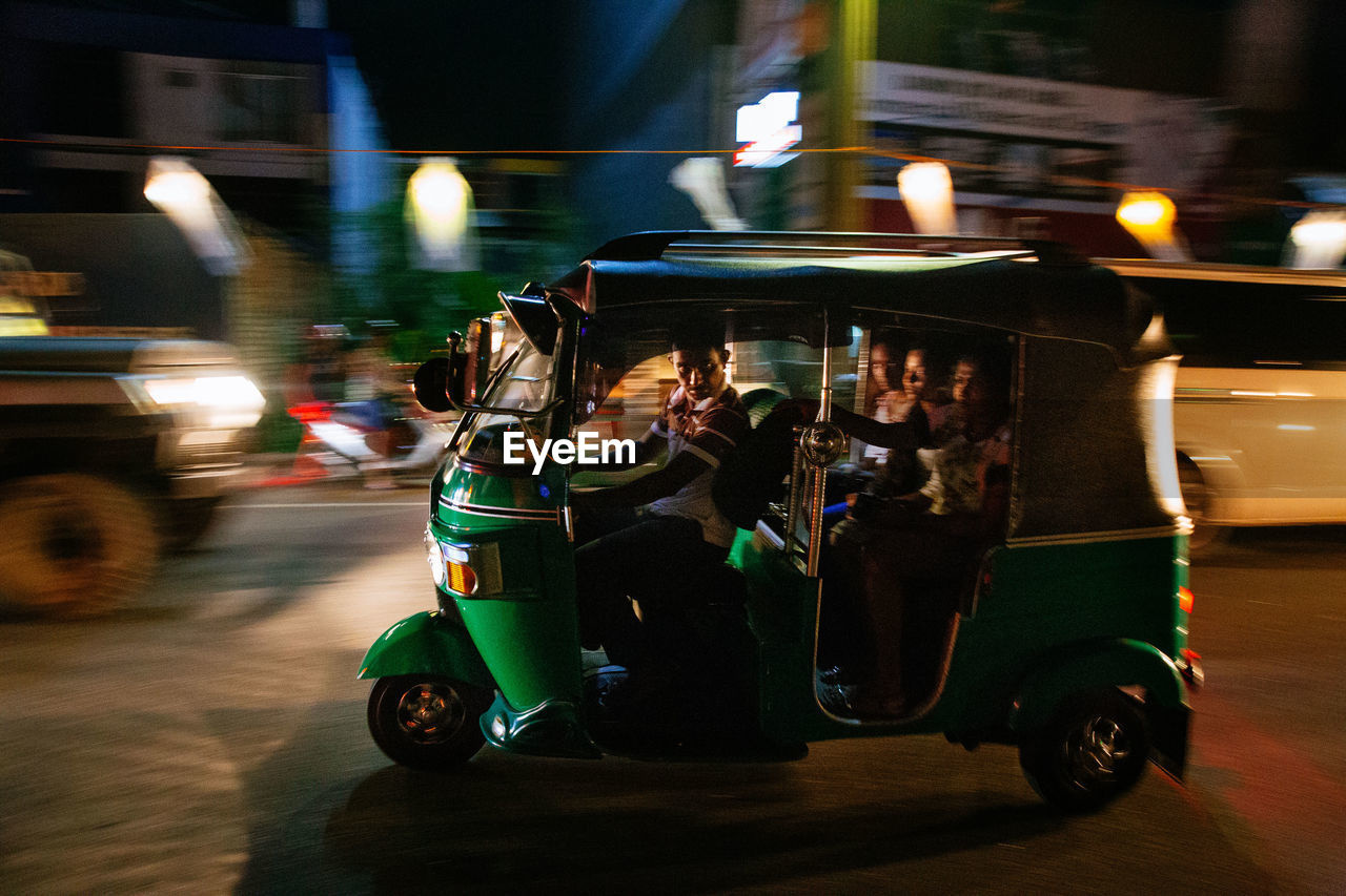 mode of transportation, transportation, land vehicle, street, illuminated, motion, real people, city, night, blurred motion, car, motor vehicle, road, people, city life, incidental people, on the move, travel, architecture, men
