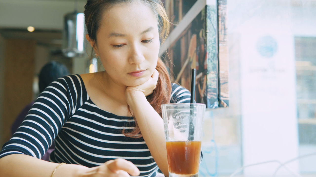 Young Woman With Drink Glass At Cafe