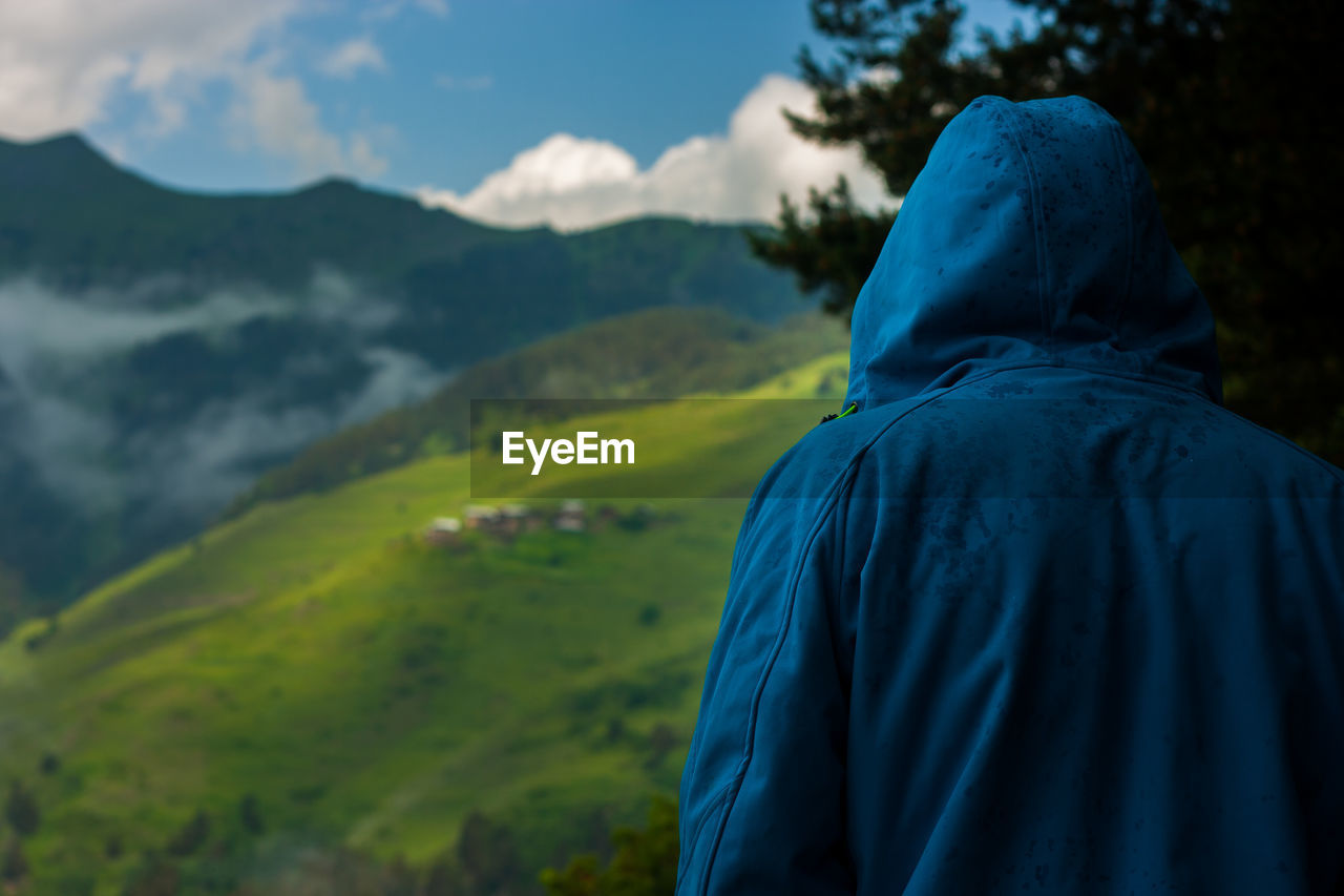 Rear View Of Person Wearing Hooded Clothing Against Mountains