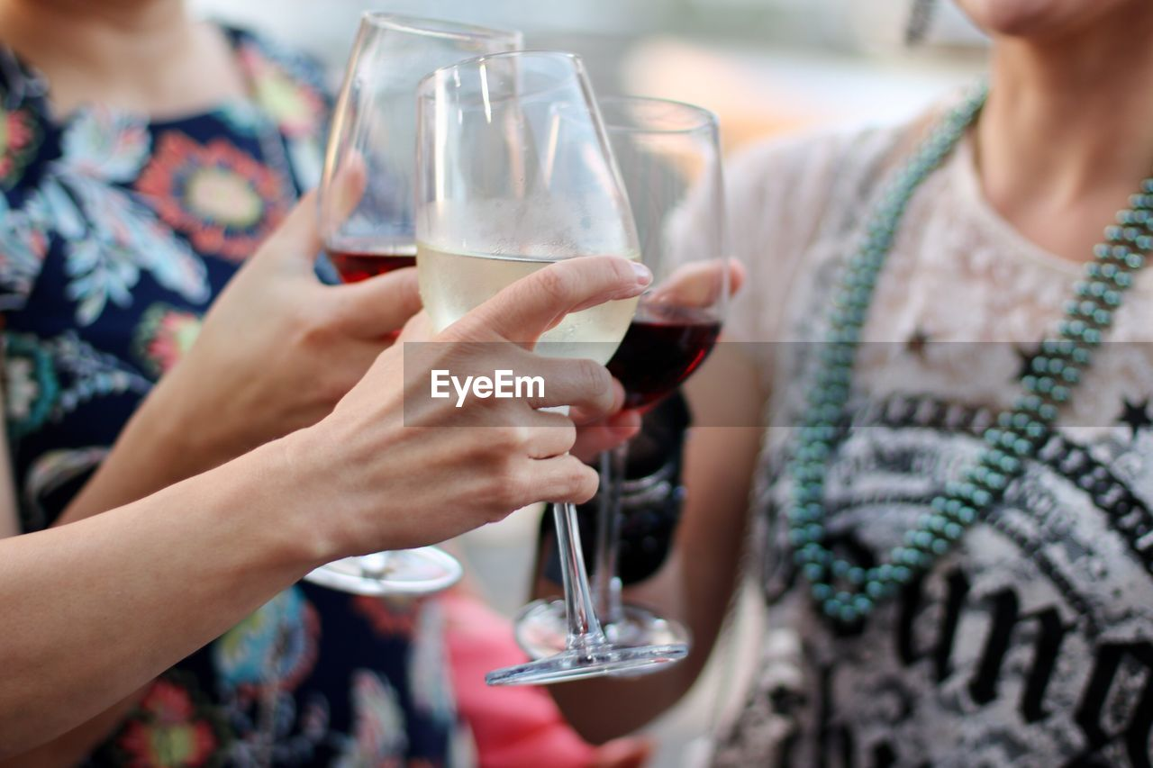 Midsection of women toasting wineglasses