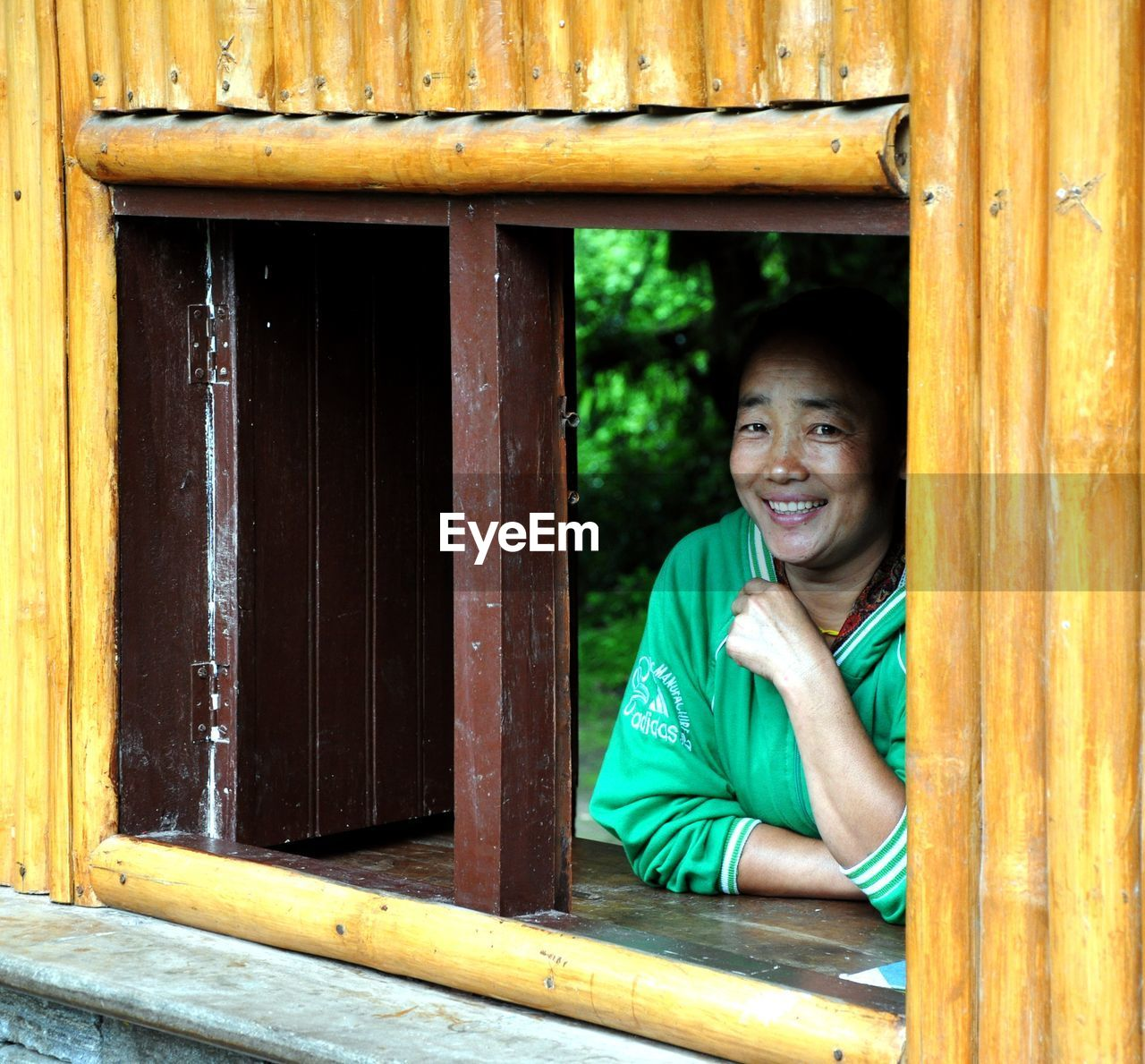 one person, looking at camera, wood - material, portrait, smiling, leisure activity, happiness, casual clothing, real people, day, front view, child, childhood, lifestyles, emotion, architecture, outdoors, window, teenager, teenage boys