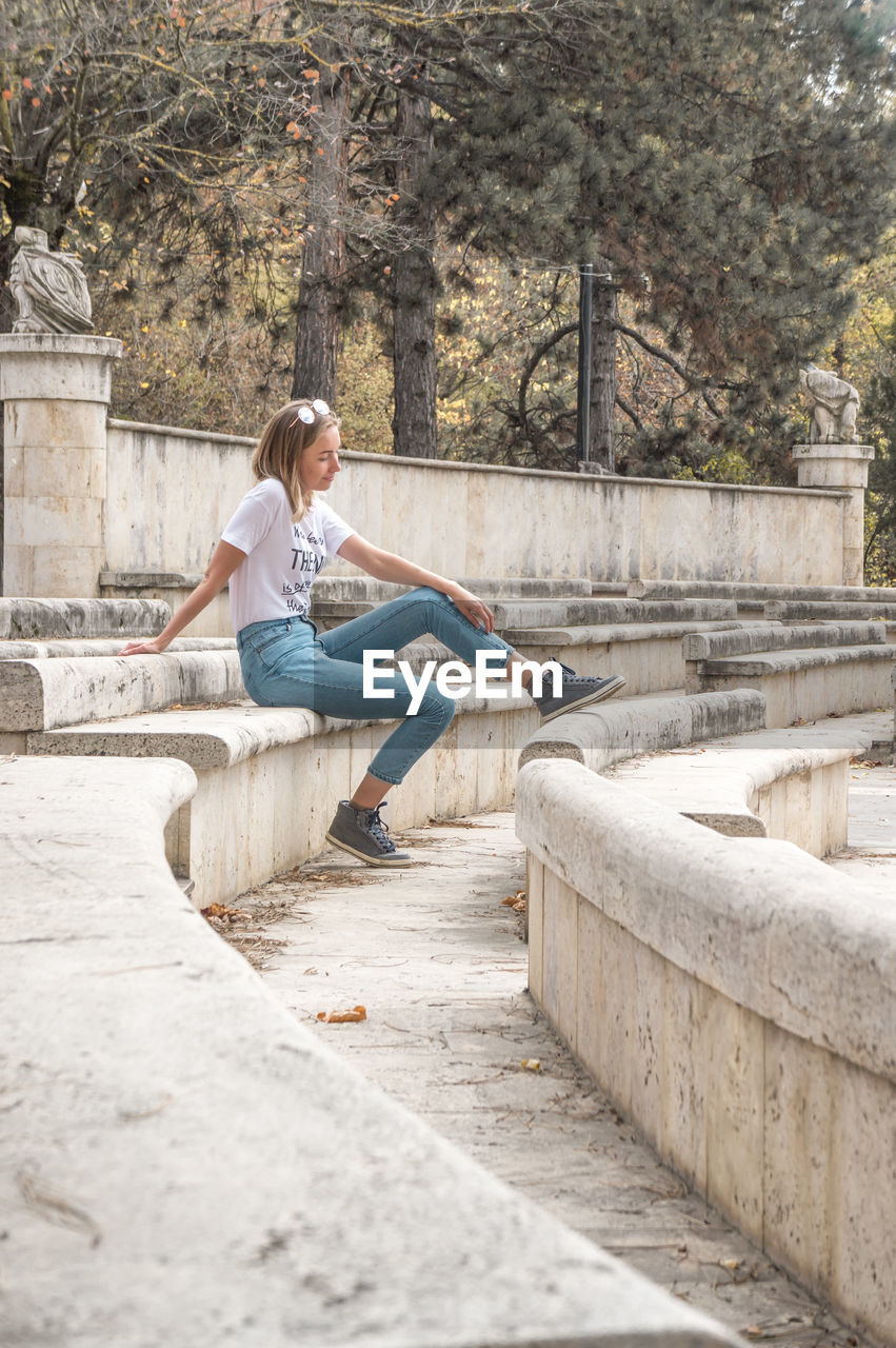 SIDE VIEW OF WOMAN SITTING ON RETAINING WALL AGAINST BUILDING