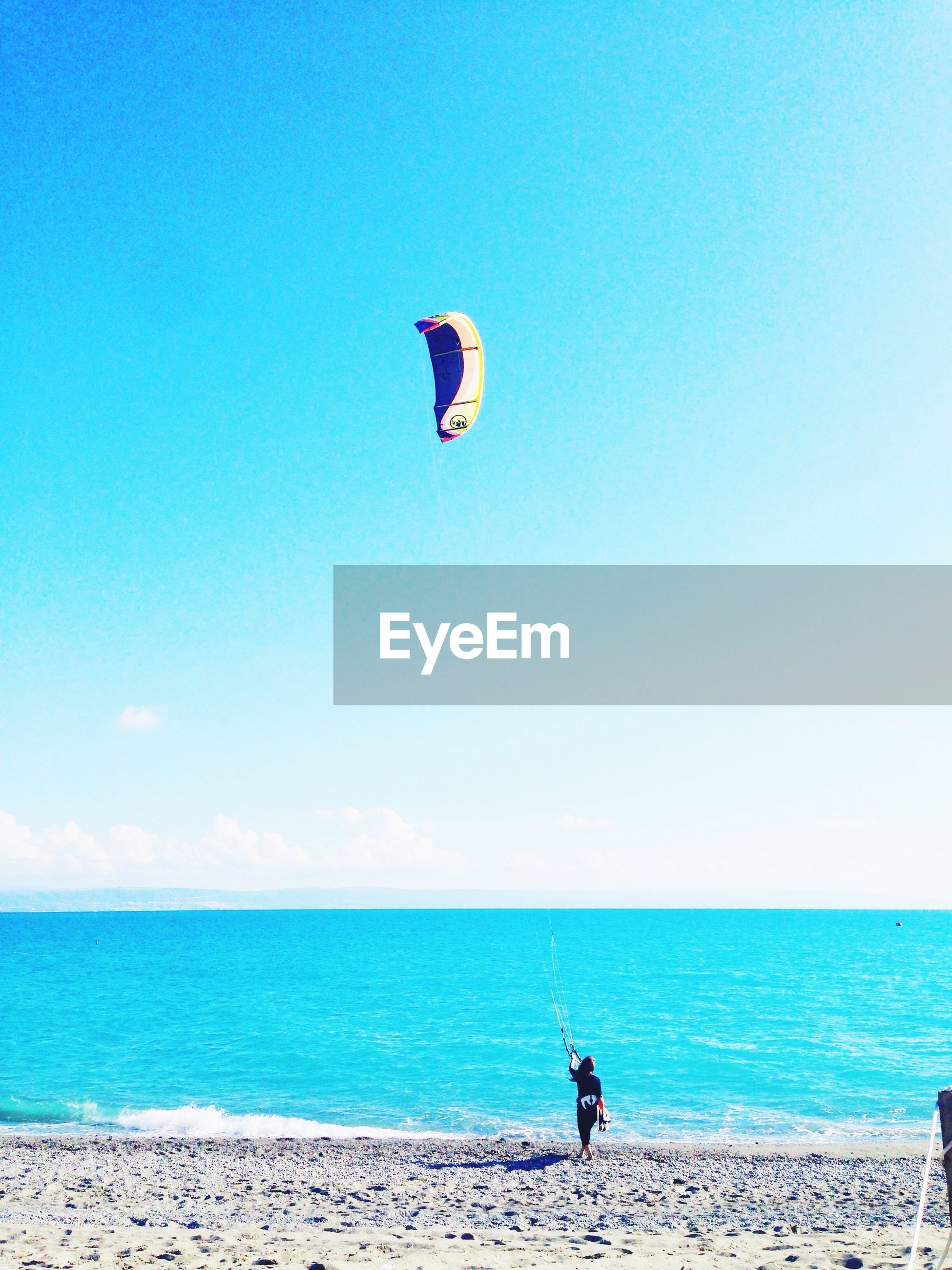 Man paragliding on beach