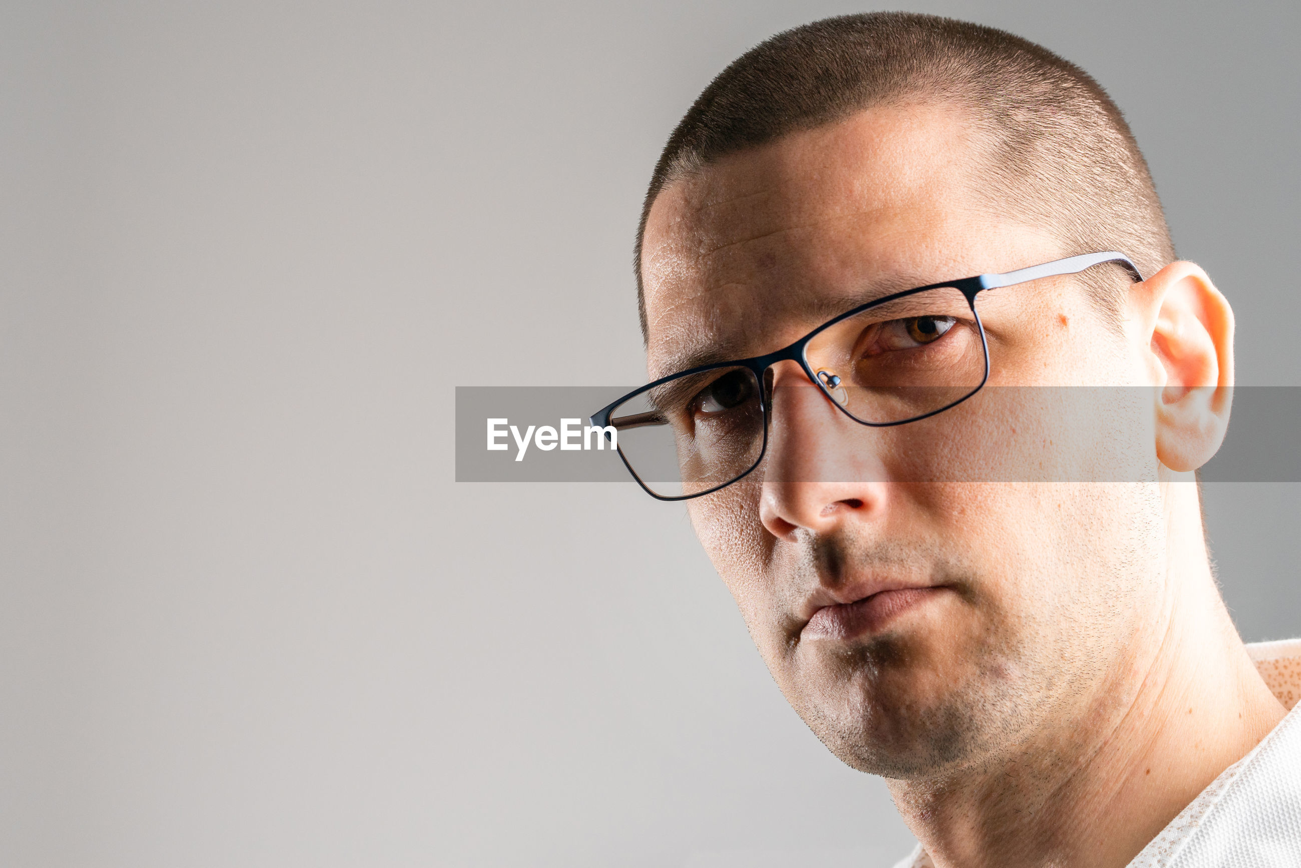 CLOSE-UP PORTRAIT OF MAN WEARING EYEGLASSES AGAINST GRAY BACKGROUND