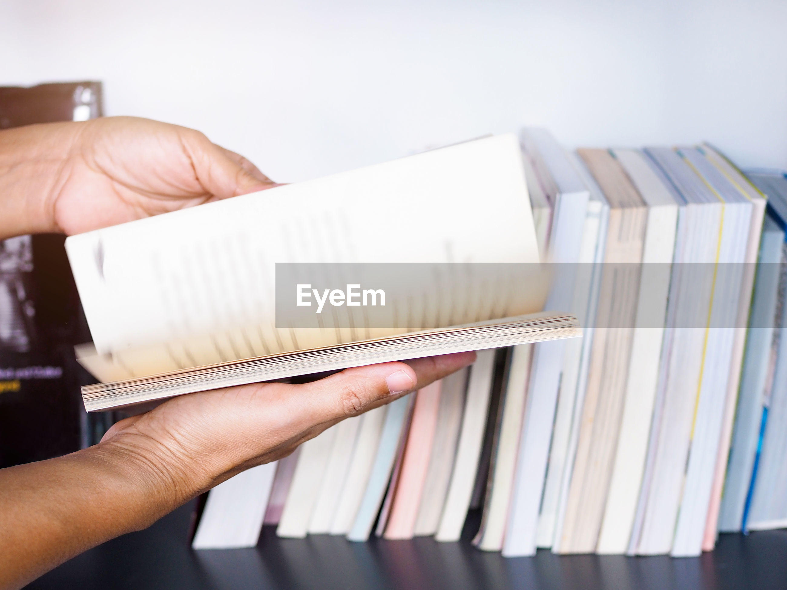 Cropped hands of person holding book
