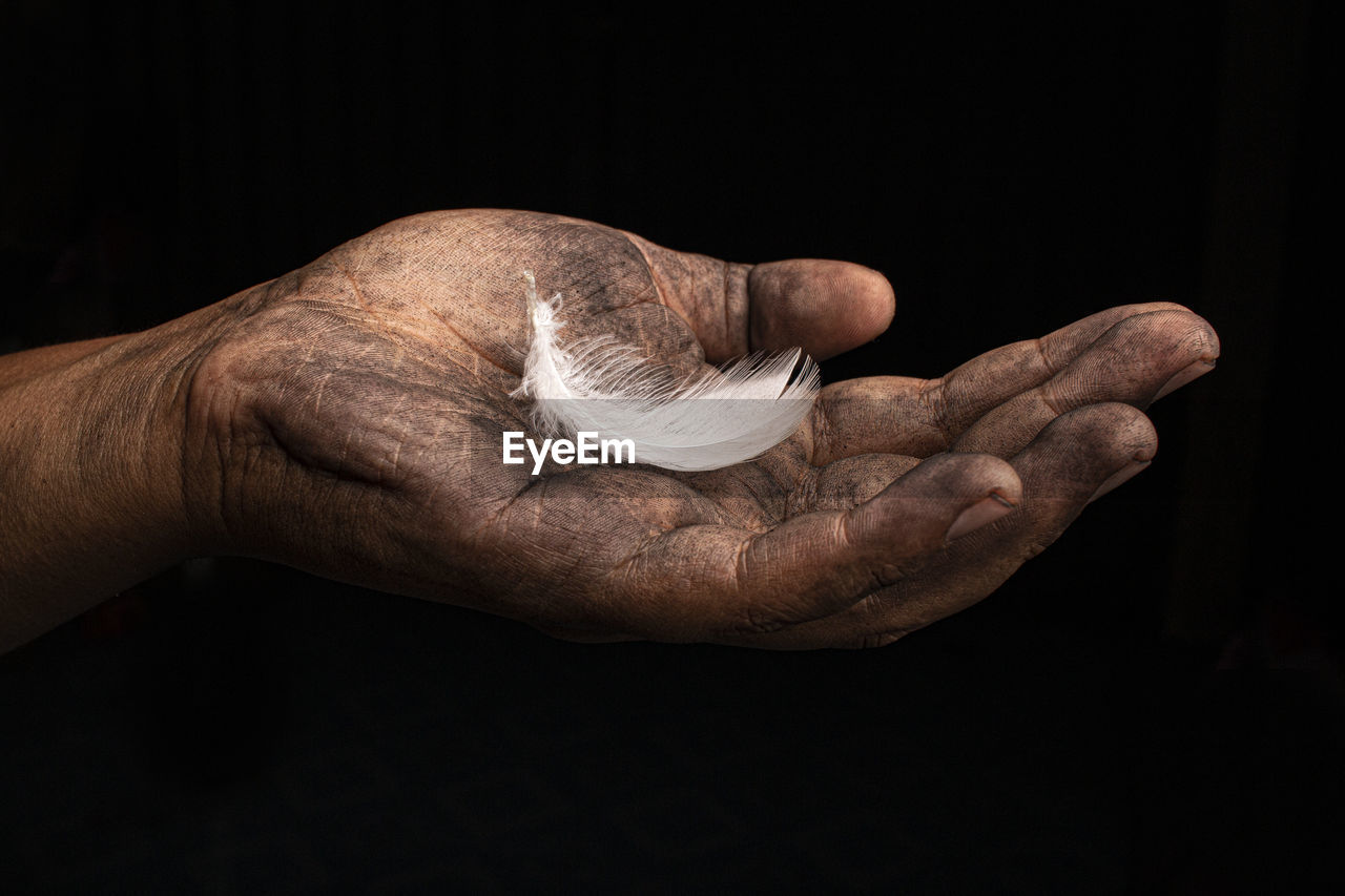 Cropped image of messy hand holding feather against black background