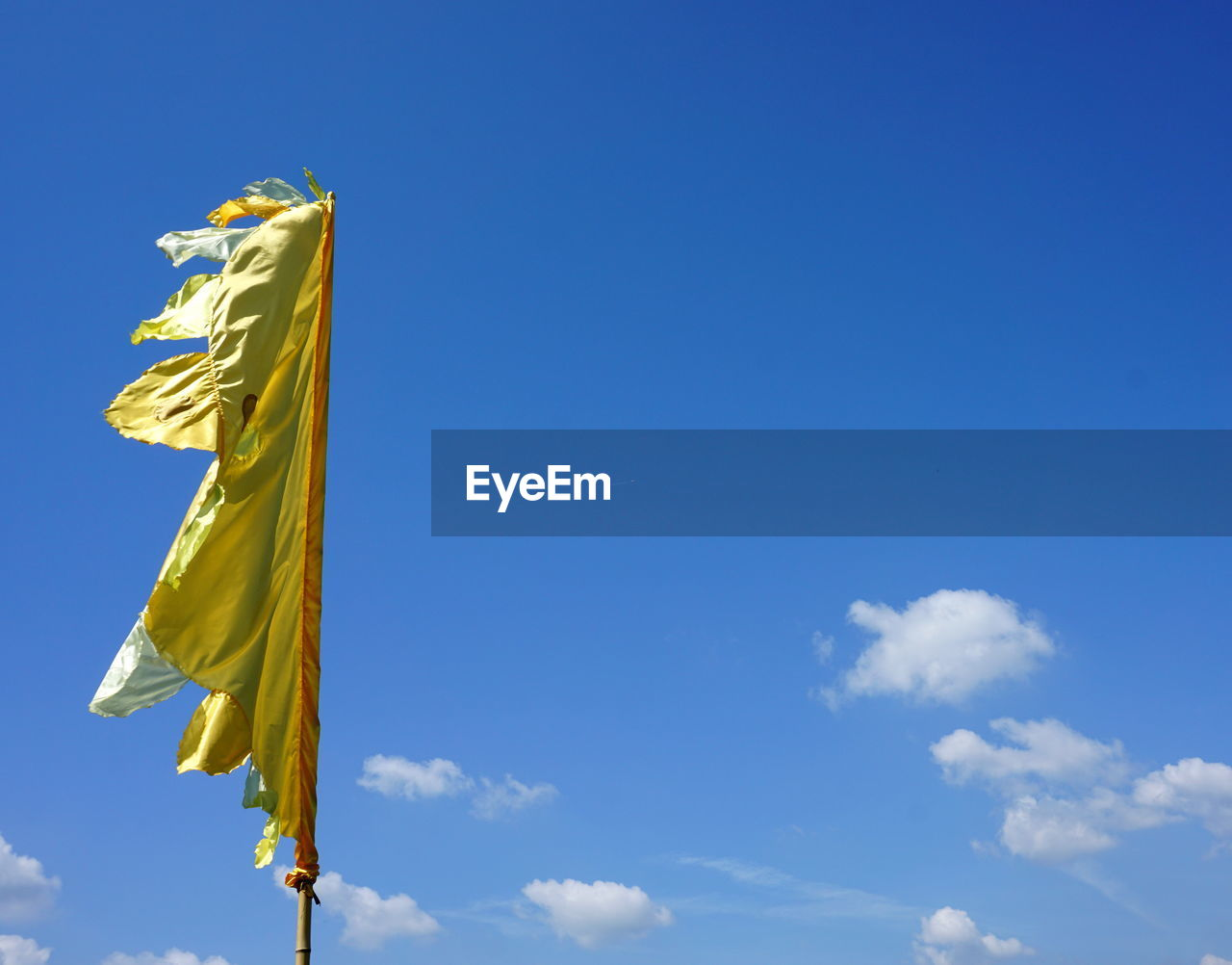 sky, blue, low angle view, cloud - sky, yellow, day, no people, nature, flag, copy space, art and craft, outdoors, belief, textile, human representation, sunlight, patriotism, spirituality, representation, religion, wind
