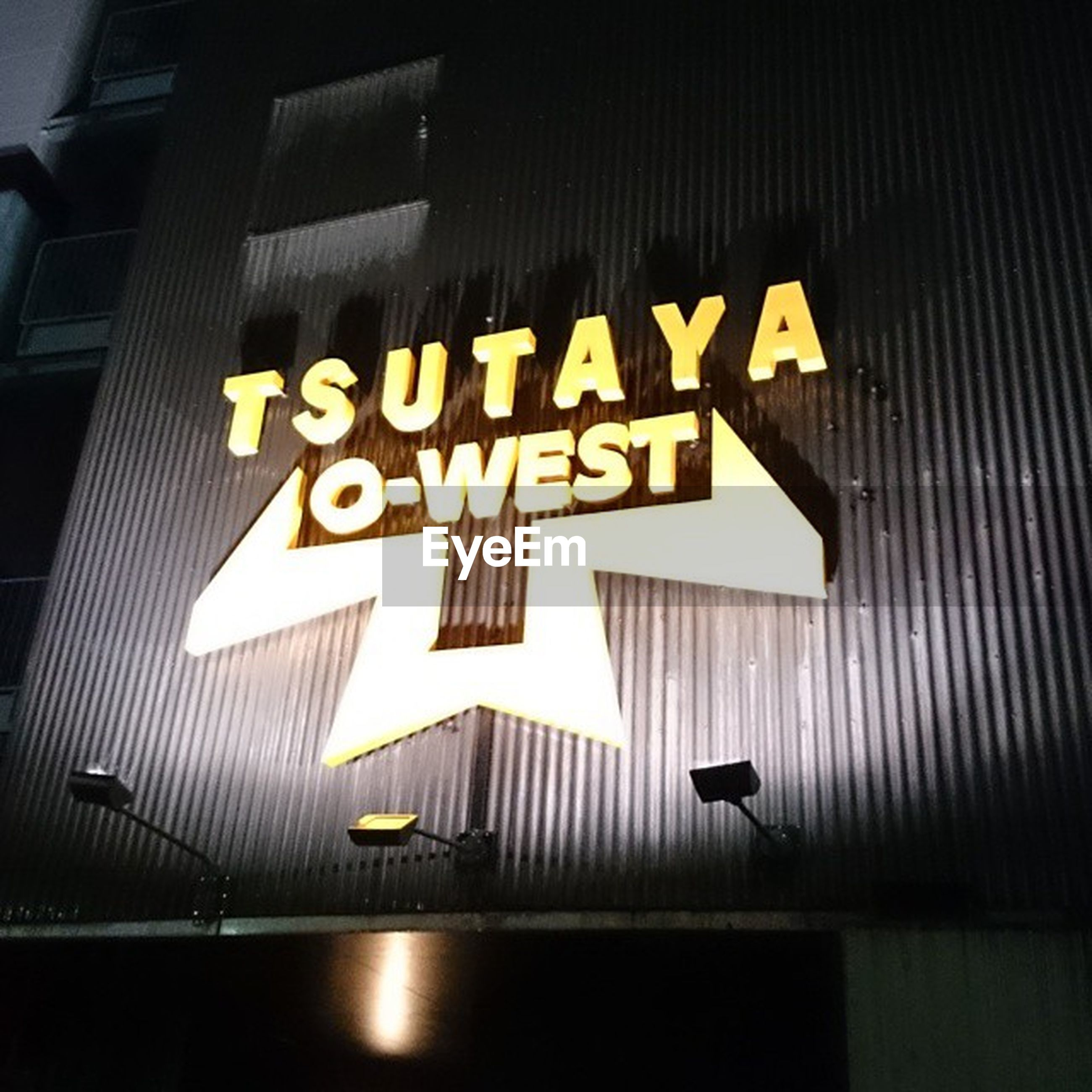 text, western script, communication, information sign, sign, illuminated, guidance, low angle view, information, capital letter, built structure, arrow symbol, directional sign, architecture, non-western script, night, road sign, building exterior, lighting equipment, commercial sign