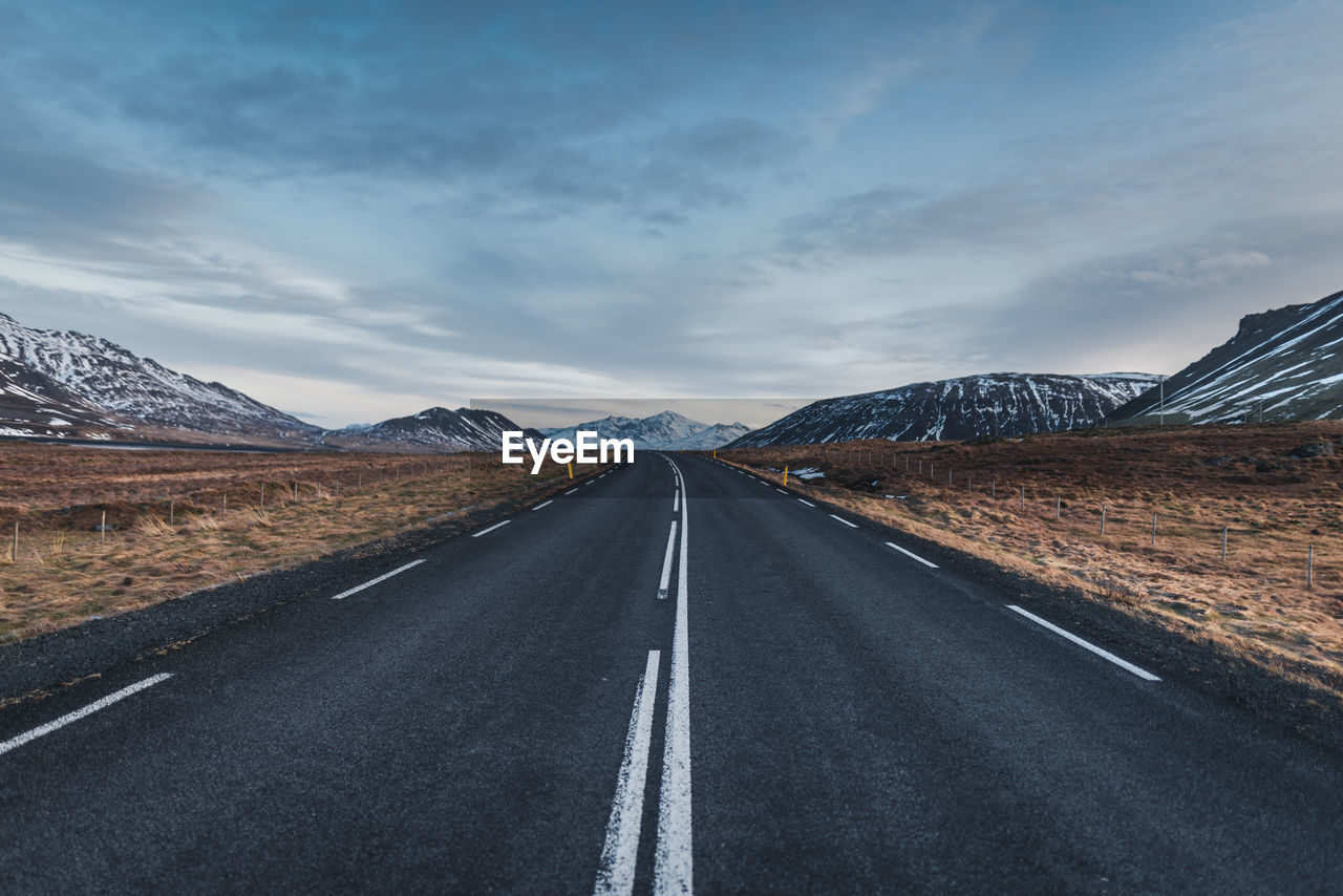 Empty road leading towards mountains against cloudy sky during winter