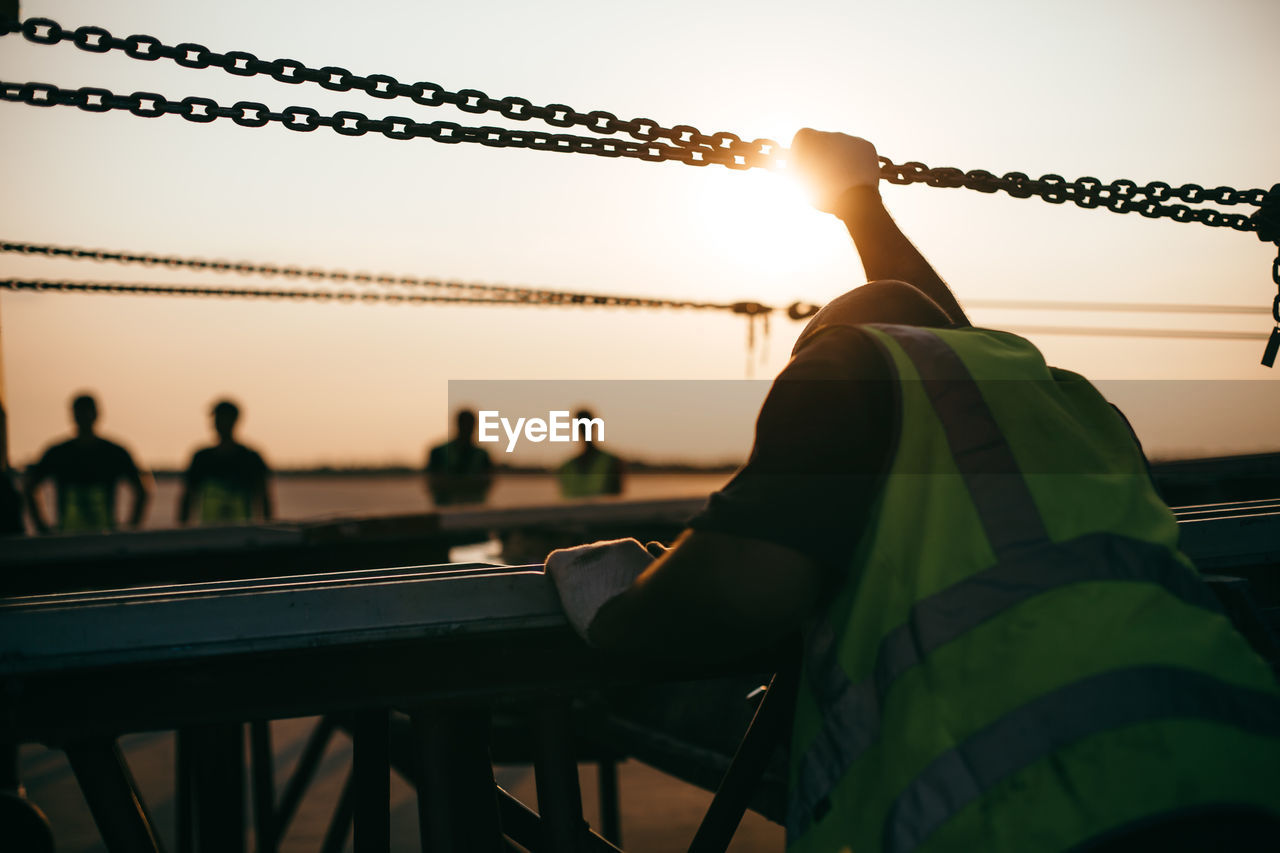 Side View Of Silhouette Man Standing By Railing Against Sky During Sunset