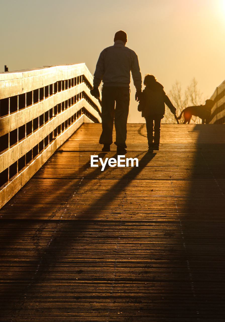 Rear View Of Man Walking With Son On Bridge Against Sky During Sunset