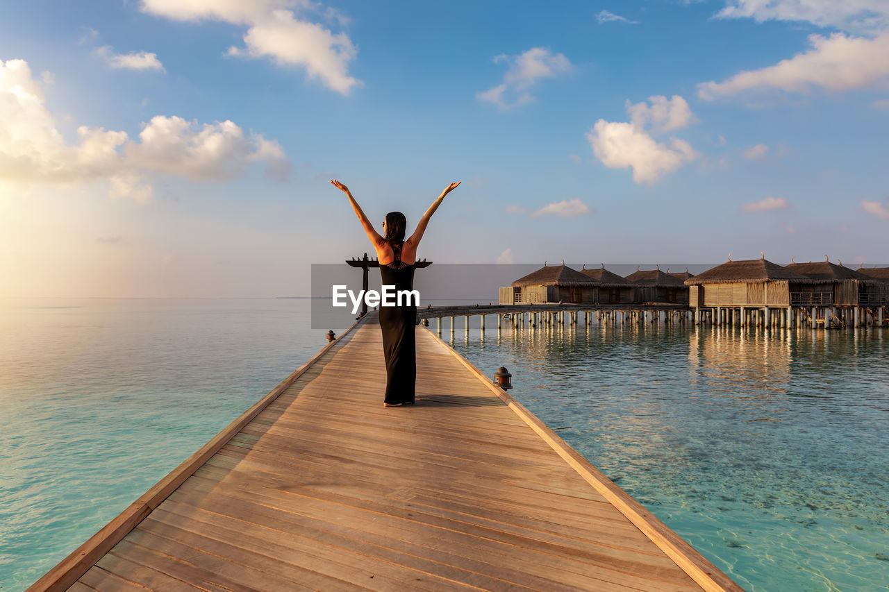 Rear View Of Woman With Arms Raised Standing On Pier Over Sea Against Sky