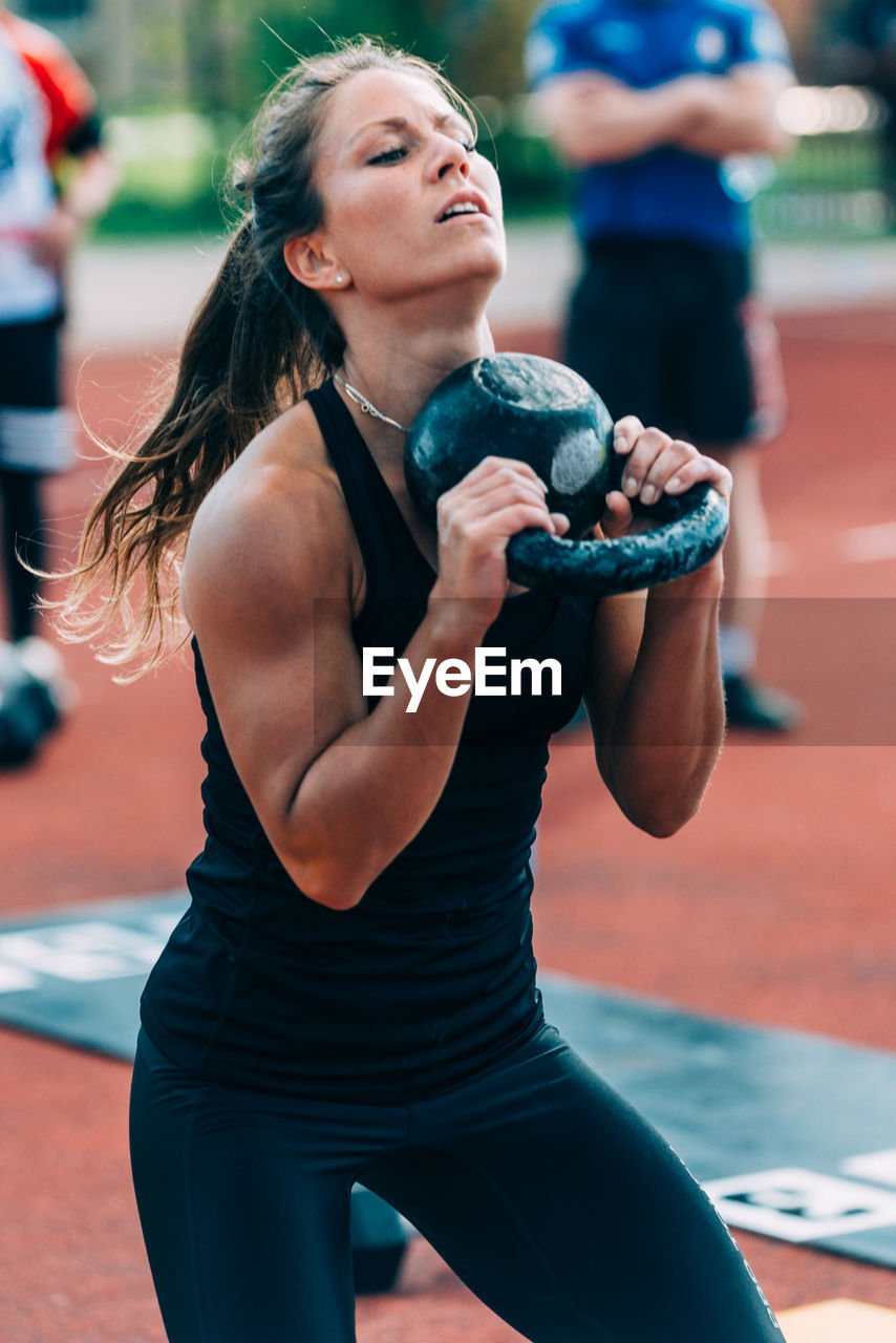 Woman Lifting Kettlebell On Running Track