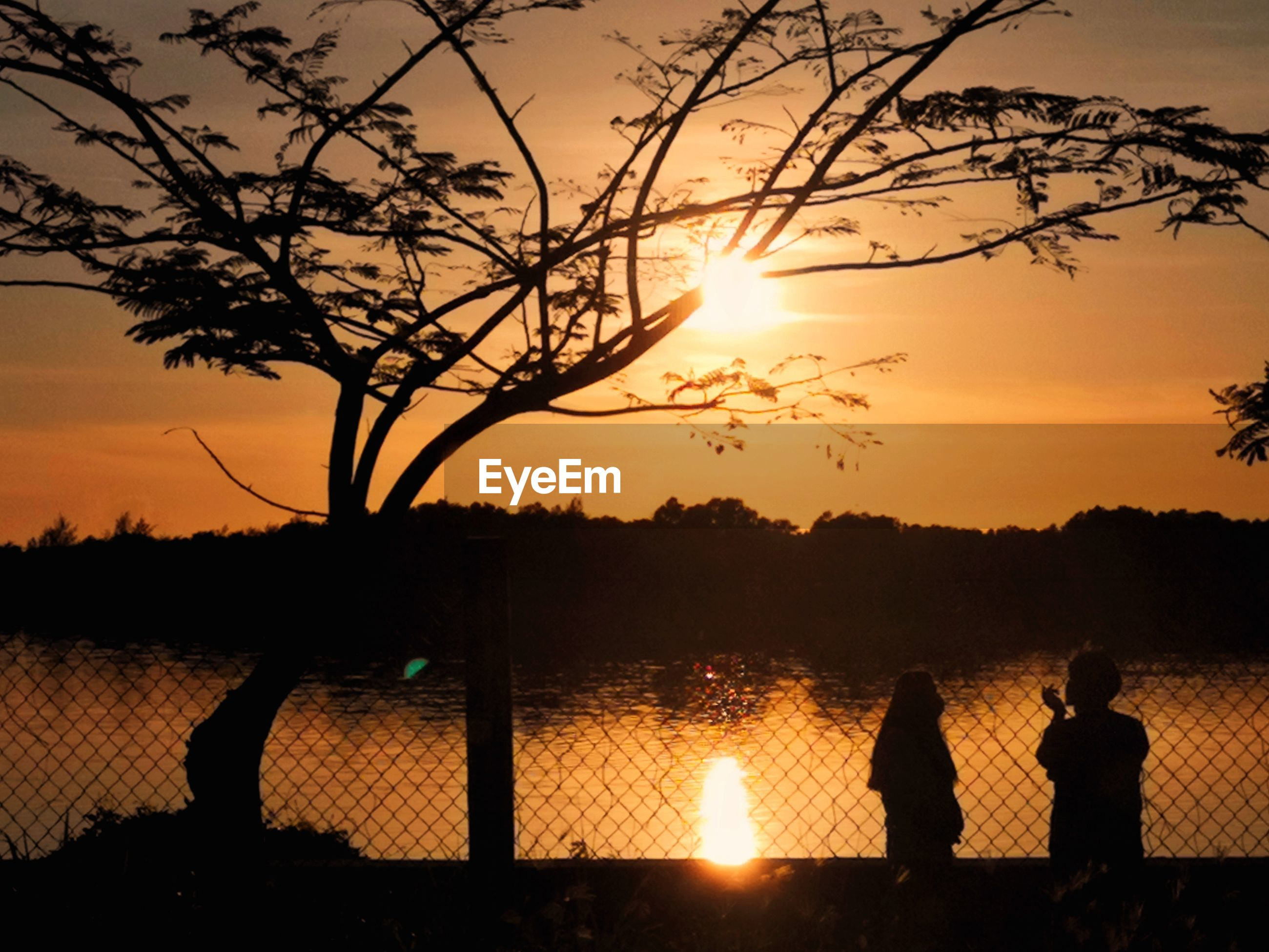 SILHOUETTE MEN BY LAKE AGAINST SKY DURING SUNSET