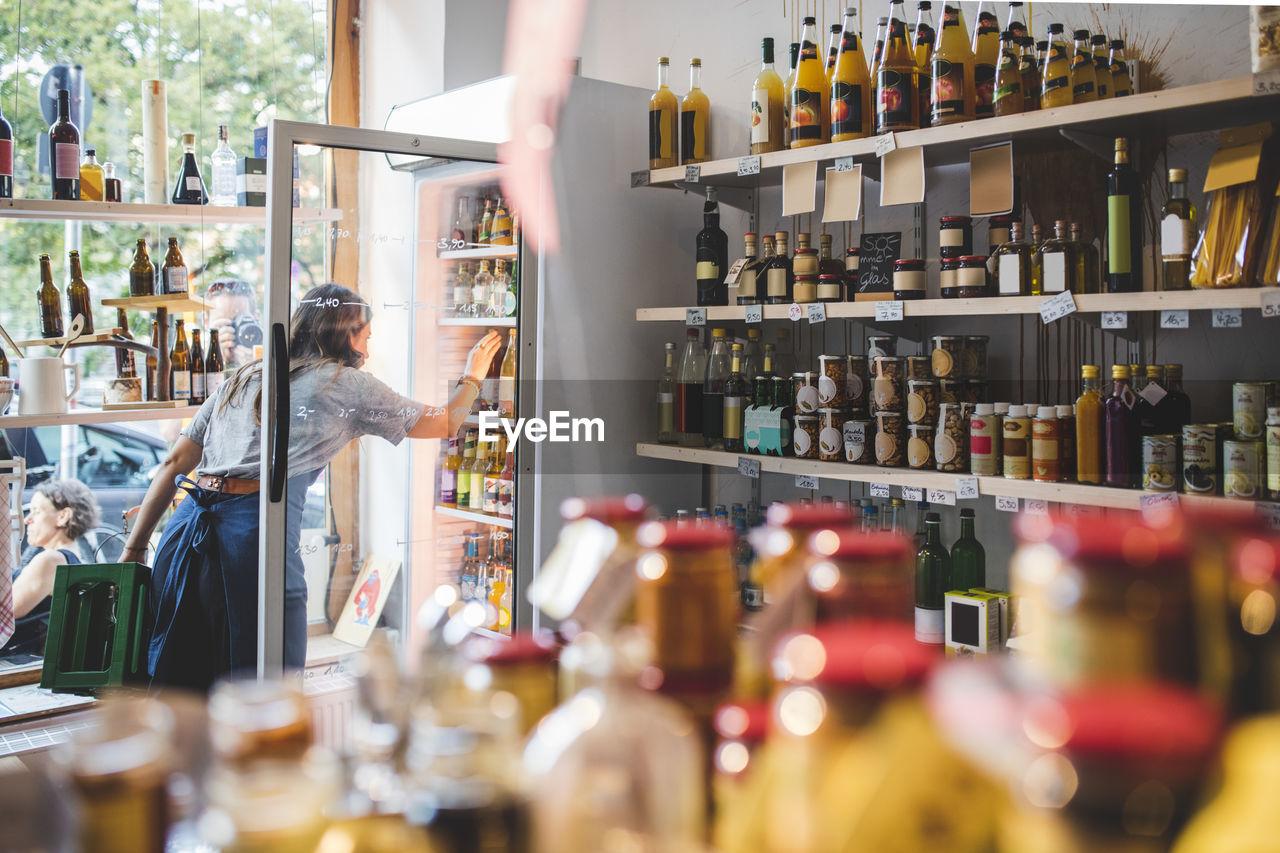 Female employee arranging bottles in refrigerator at deli