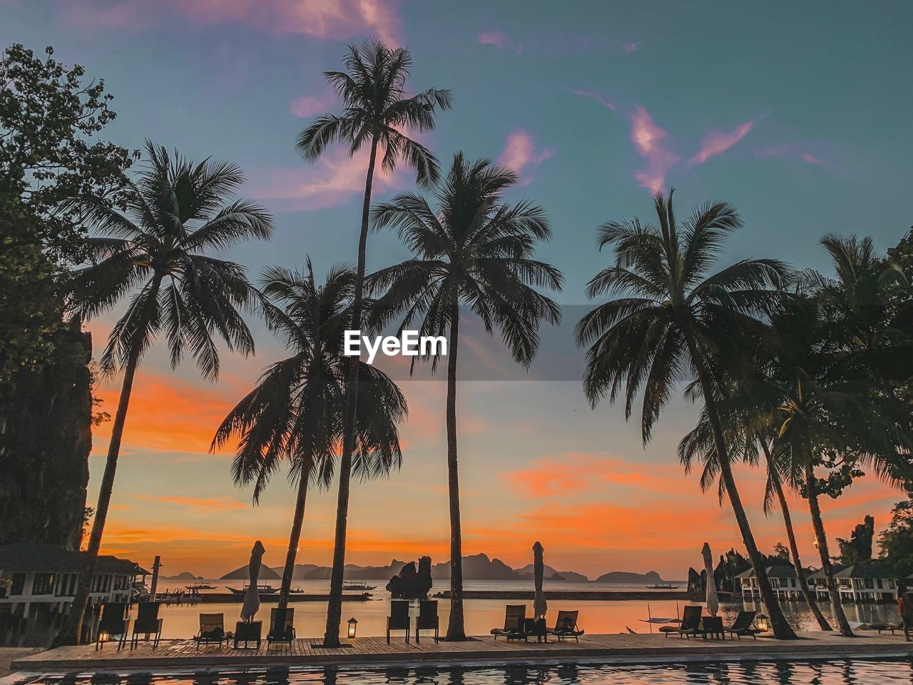 sky, sunset, water, palm tree, tropical climate, orange color, silhouette, tree, beauty in nature, nature, scenics - nature, plant, cloud - sky, sea, beach, tranquil scene, nautical vessel, outdoors, tranquility, no people, coconut palm tree
